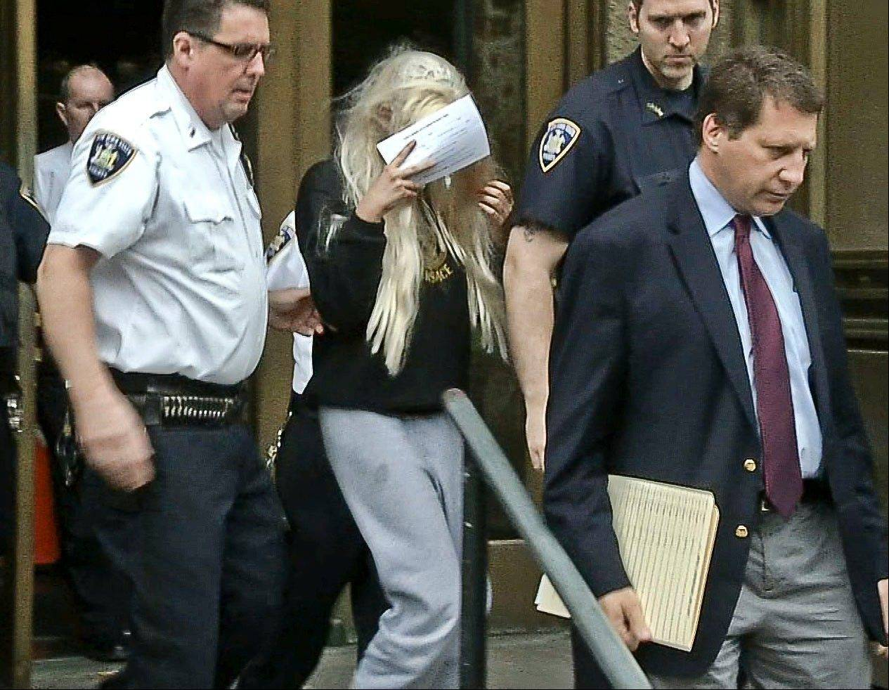 Actress Amanda Bynes, center, wearing sweats and a blonde wig, shields her face as she is escorted after a Manhattan criminal court appearance on Friday in New York.