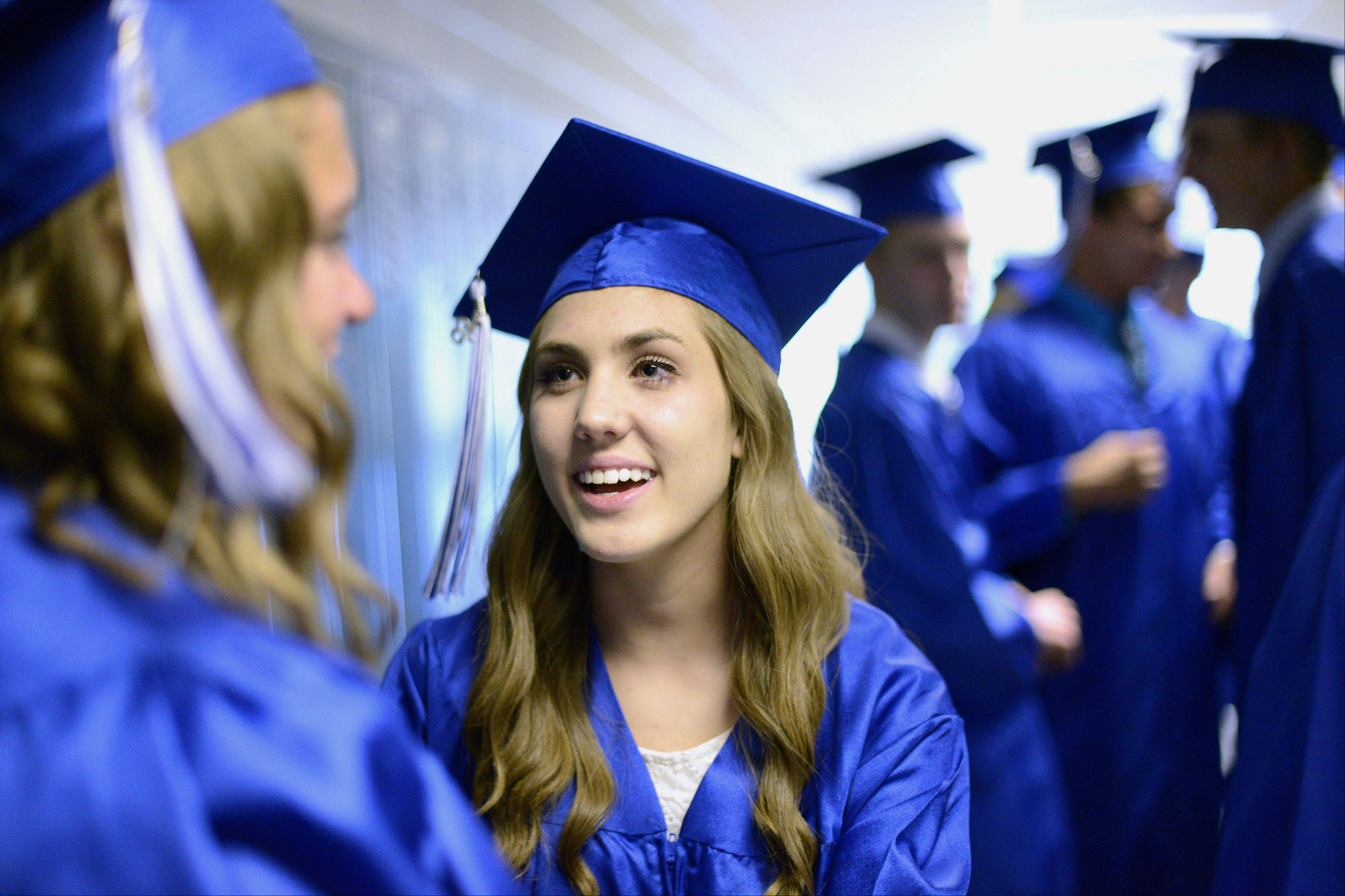 Elizabeth Farwell, 18, of West Dundee talks with a classmate while they line up for the commencement ceremony.