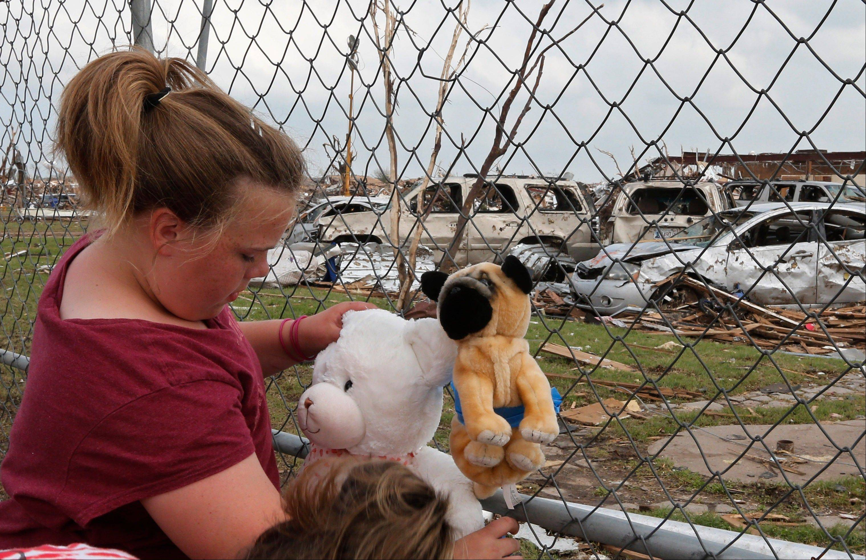 Ashlyn Kelley, age eleven, who is in the fifth grade and was in the Plaza Towers elementary school when the Moore, Okla. tornado hit, ties stuffed animals Friday to the perimeter fence as a memorial to the seven students who died.