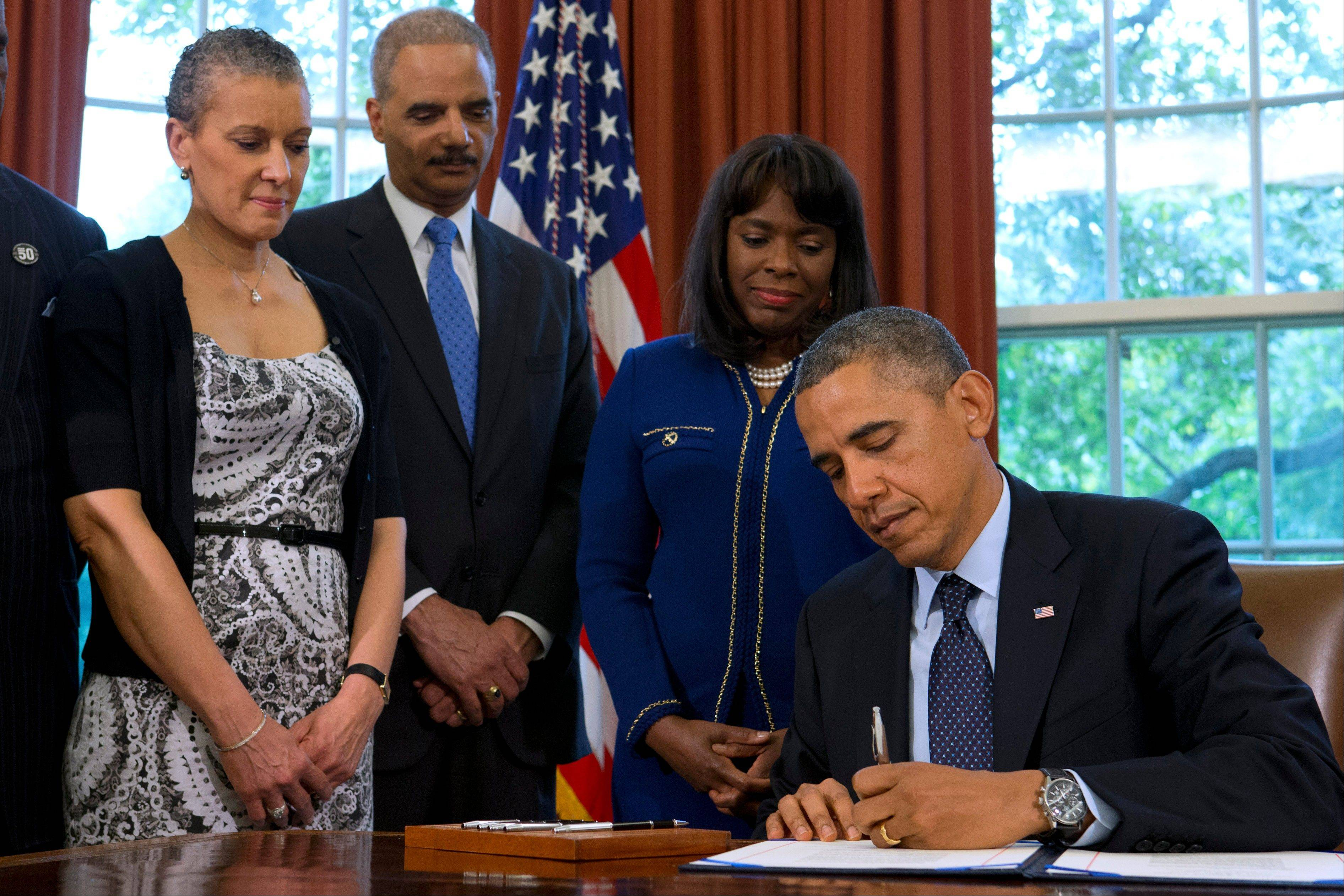 President Barack Obama signs a bill Friday designating the Congressional Gold Medal commemorating the lives of the four young girls killed in the 16th Street Baptist Church Bombing of 1963, in the Oval Office of the White House in Washington. Watching, from left are, Dr. Sharon Malone, wife of Attorney General Eric Holder; Attorney General Eric Holder and Rep. Terri Sewell, a Democratic sponsor of the bill.