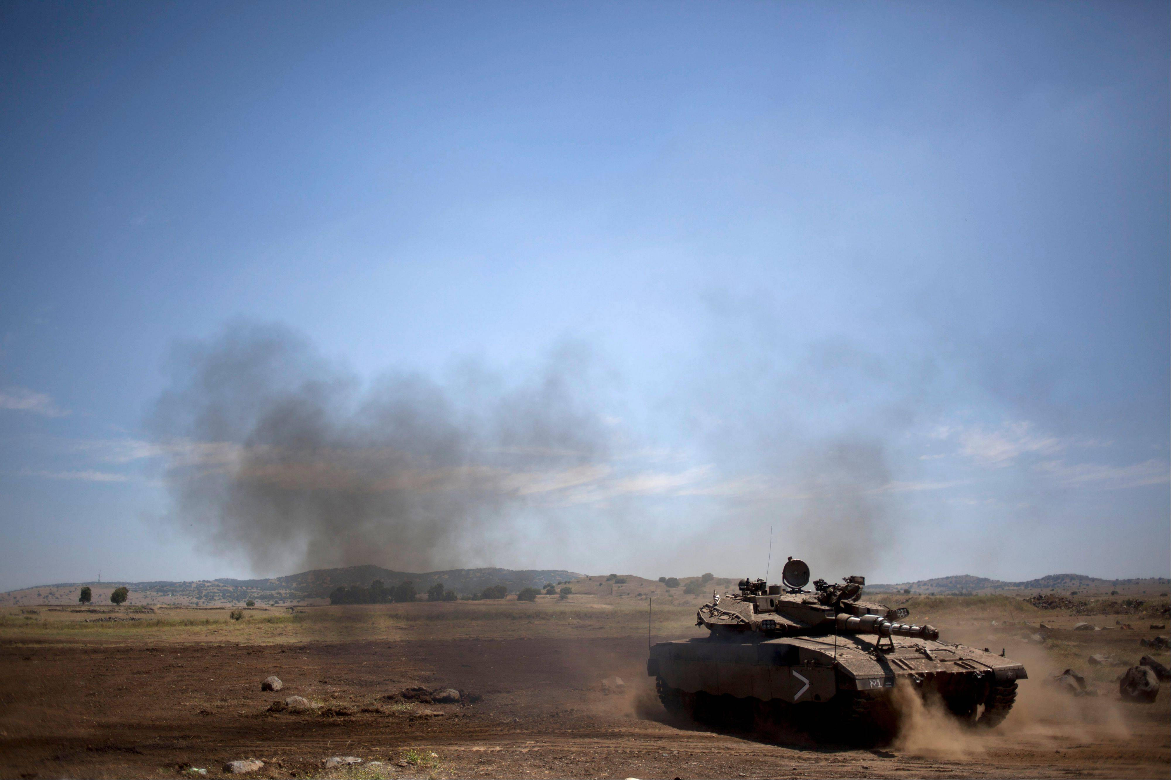 An Israeli soldier drives a tank Wednesday to be parked on a training ground in the Israeli controlled Golan Heights, near the border with Syria.