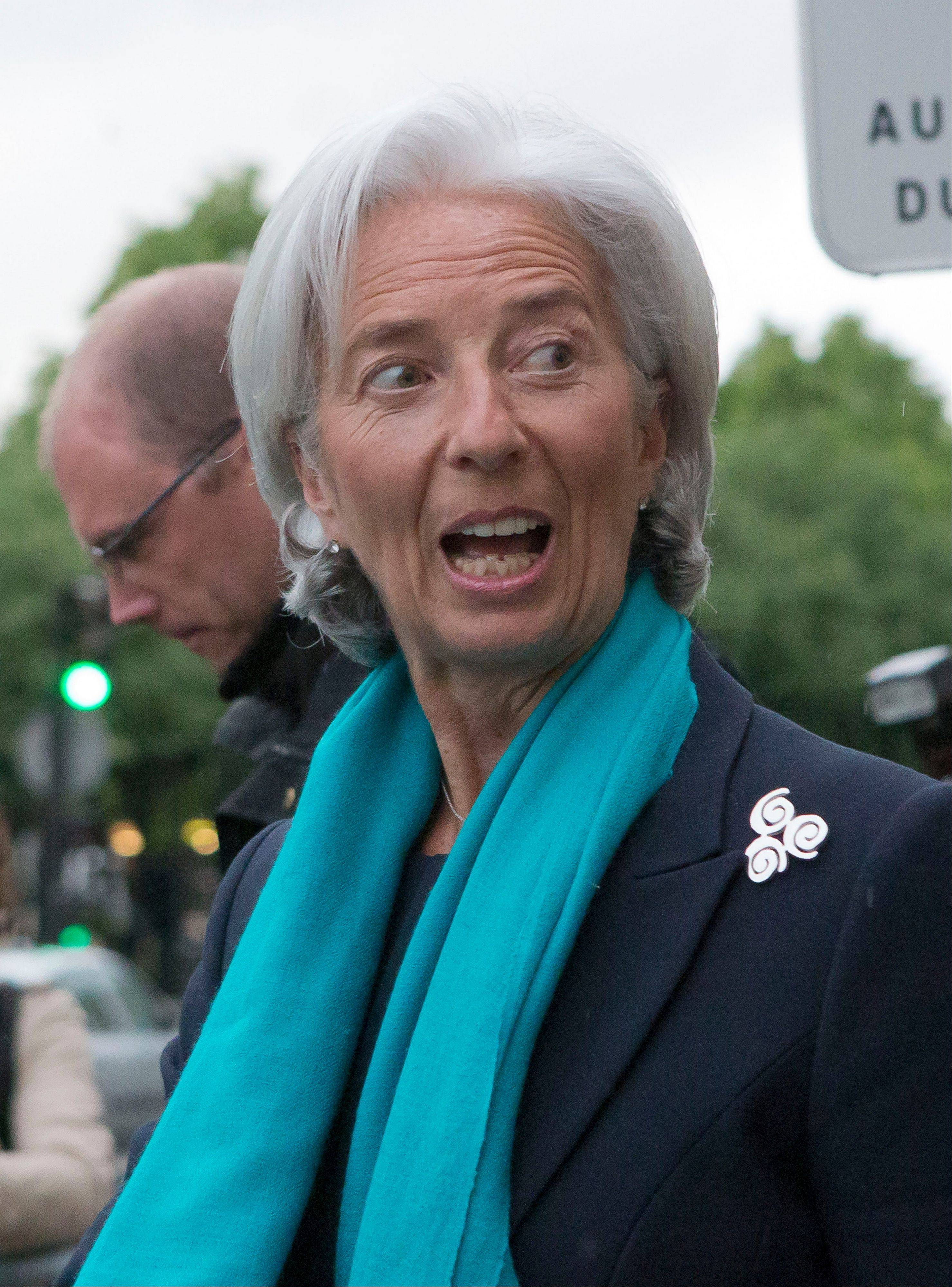 Head of the International Monetary Fund, Christine Lagarde, reacts Thursday as she leaves a special court accompanied by a police officer in Paris.