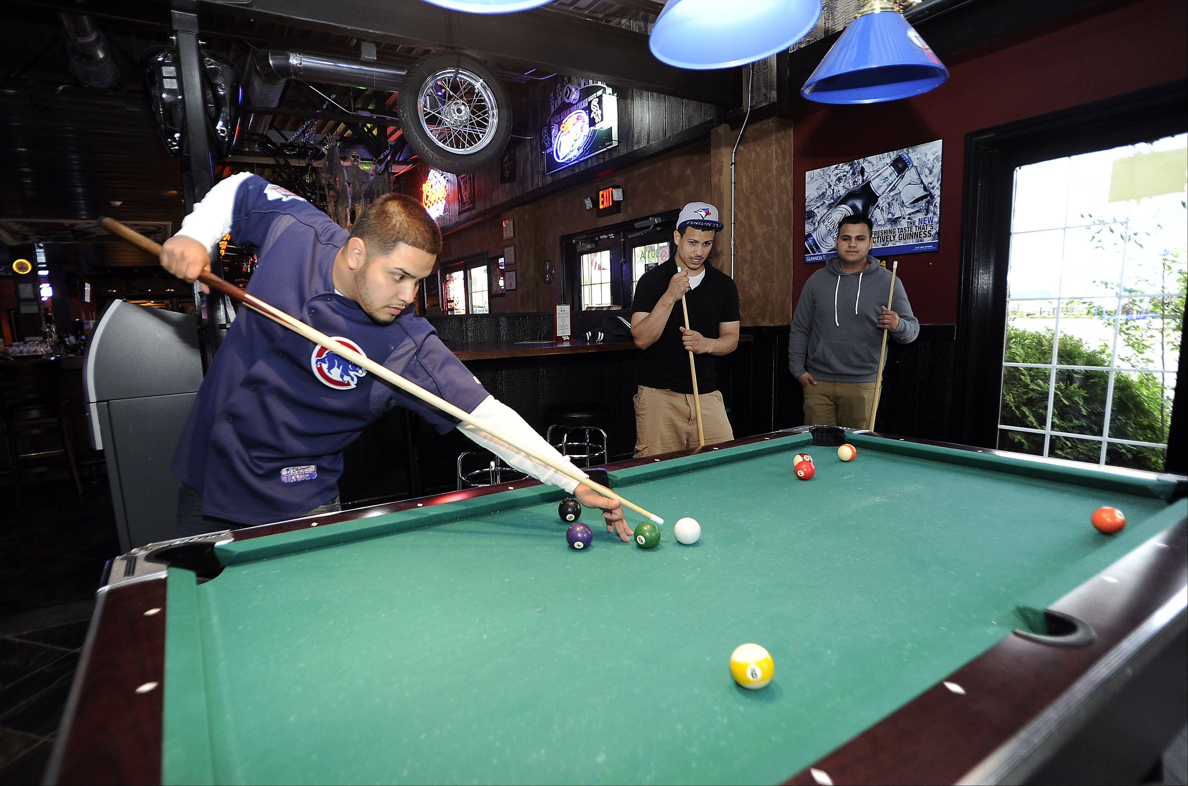 Ramon Hernandez plays pool with friends at Alley 64 in Palatine.