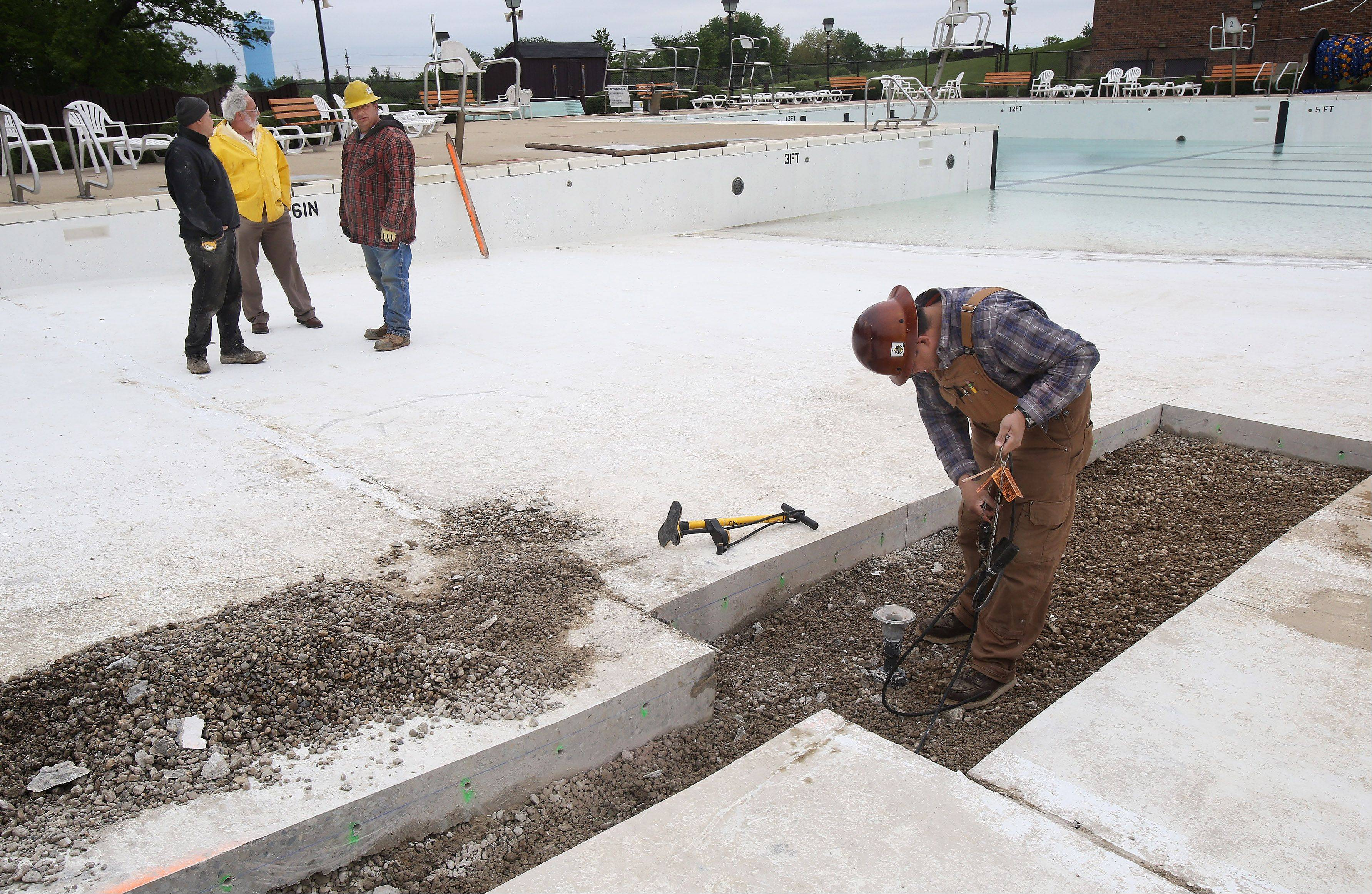 Plumber Ben Murillo, of Fountain Technologies, right, checks the repairs of the pipes under the pool at the Round Lake Area Park District Aquatic Center Thursday. The repairs have caused a delay in the center's opening, which is not expected to be June 15.