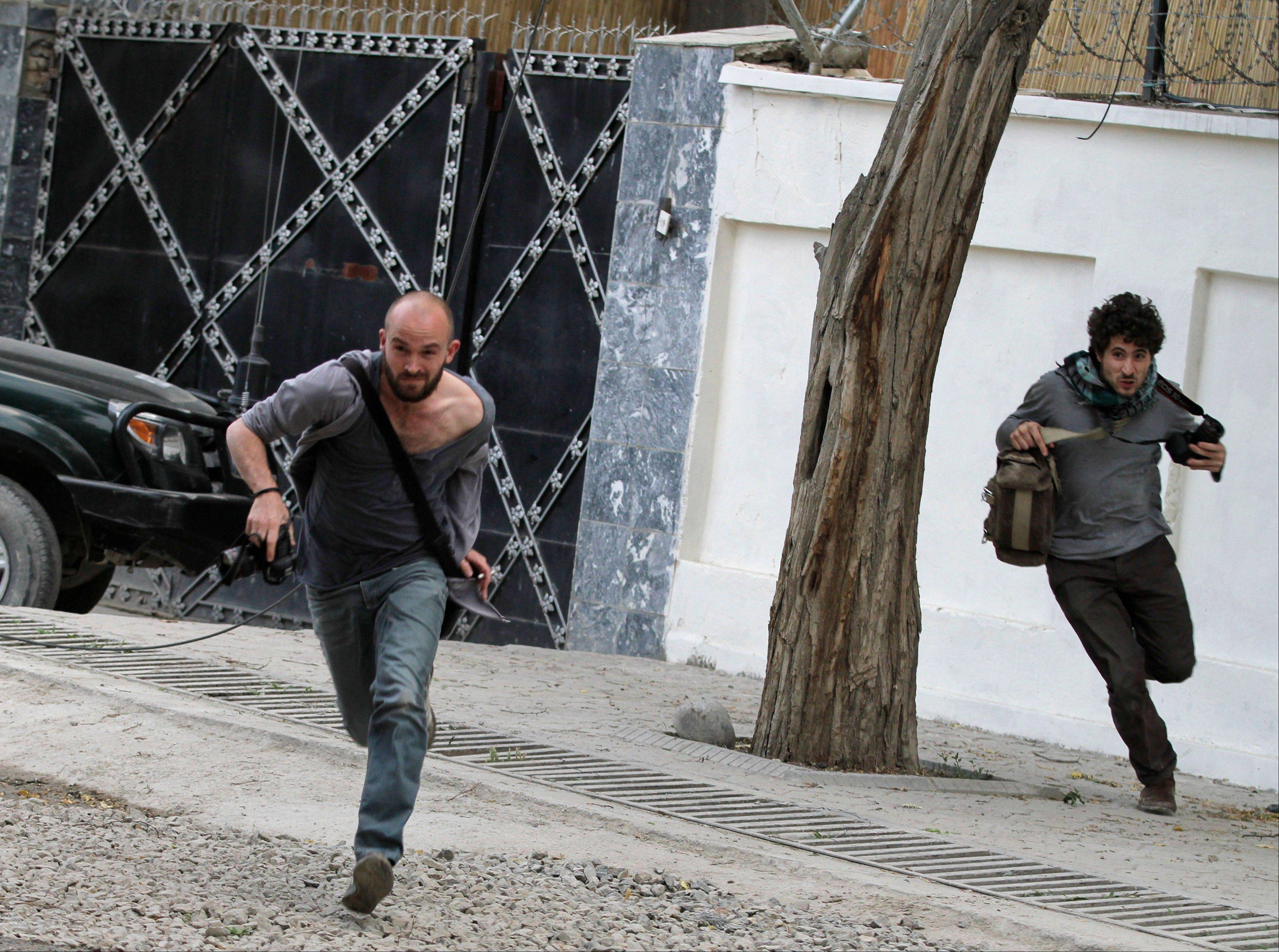 Photographers run for cover Friday following a suicide attack and ensuing gunbattle in Kabul, Afghanistan.