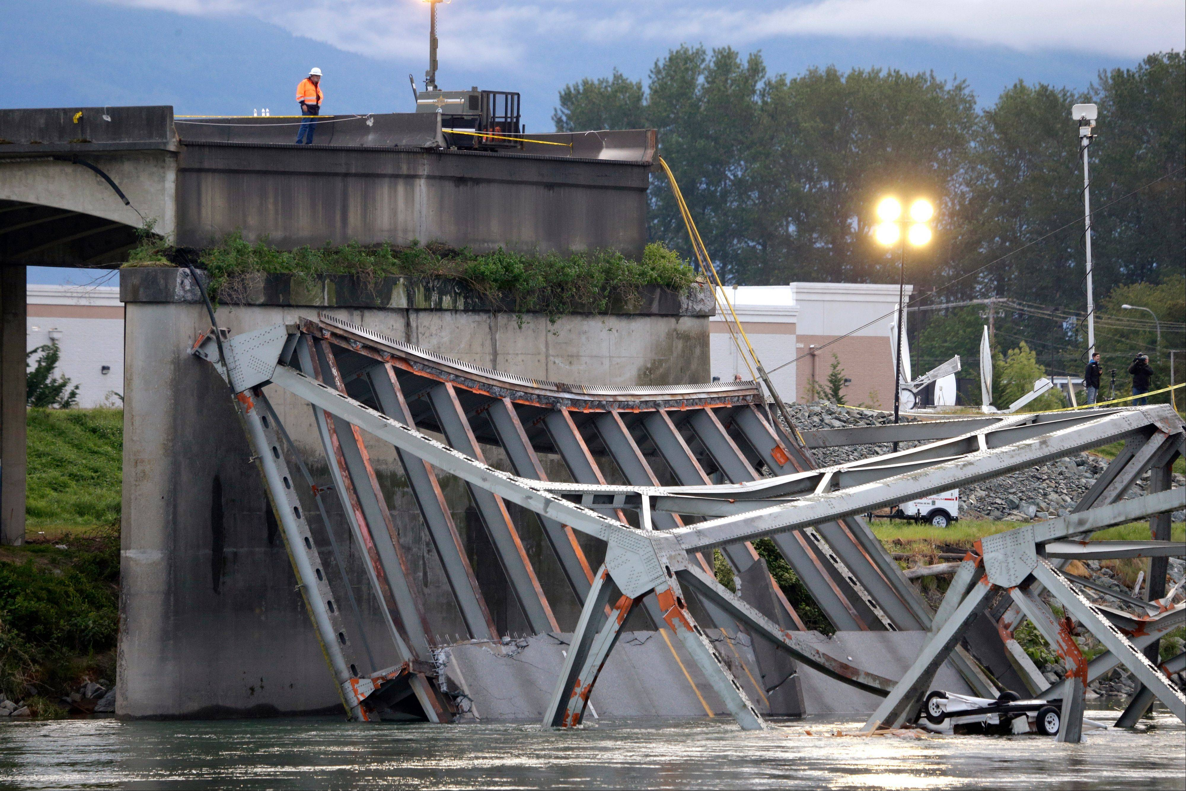 A worker looks at the collapsed portion of the Interstate 5 bridge at the Skagit River in Mount Vernon, Wash. A truck carrying an oversize load struck the four-lane bridge on the major thoroughfare between Seattle and Canada, sending a section of the span and two vehicles into the Skagit River below Thursday.