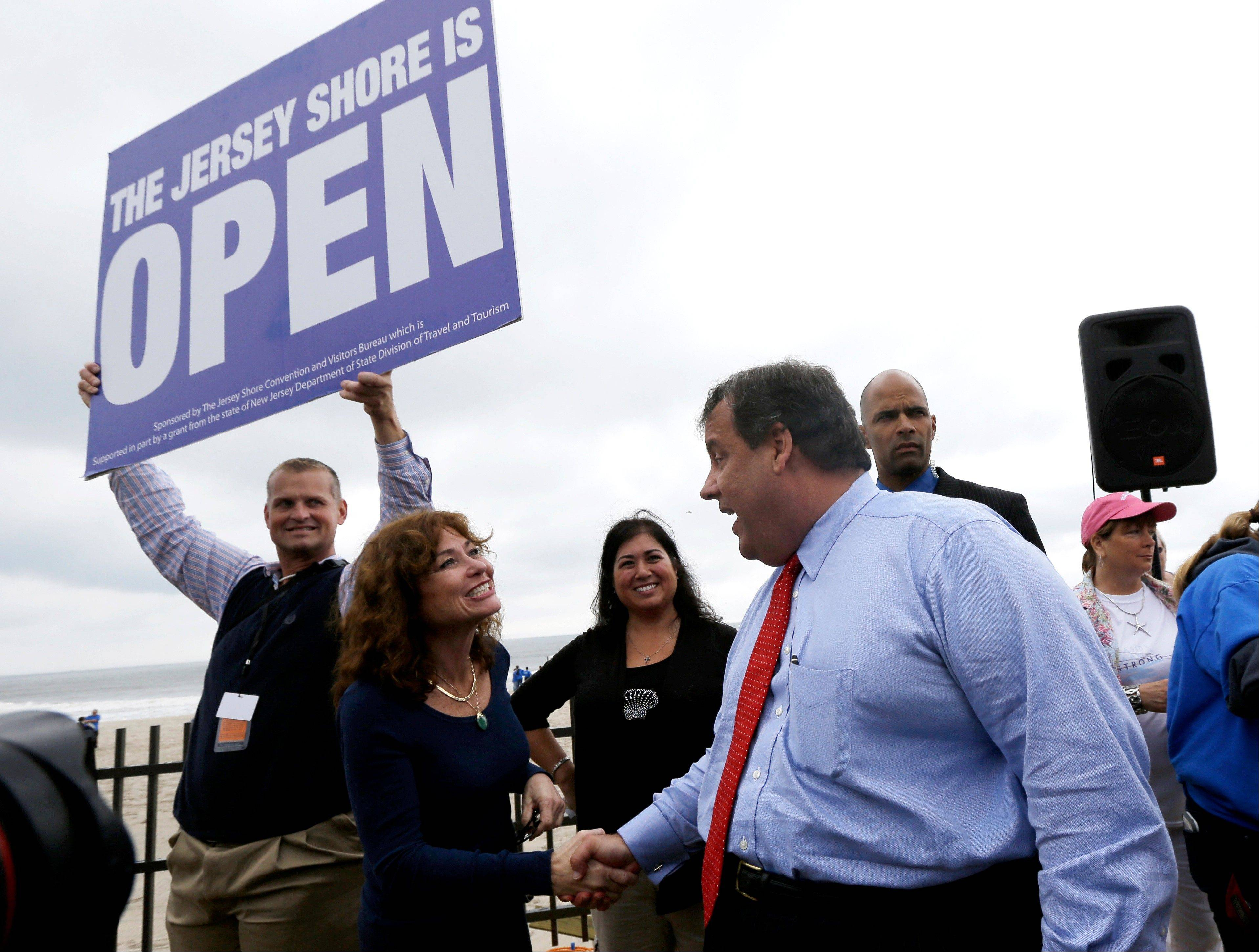 New Jersey Gov. Chris Christie, right, talks to Carla Pilla, of Seaside Heights, N.J., while Robert Hilton, left, executive director of the Jersey Shore Convention and Visitor's Bureau, holds a sign, Friday, May 24, 2013, in Seaside Heights, N.J. Christie cut a ribbon to symbolically reopen the state's shore for the summer season, seven months after being devastated by Superstorm Sandy.