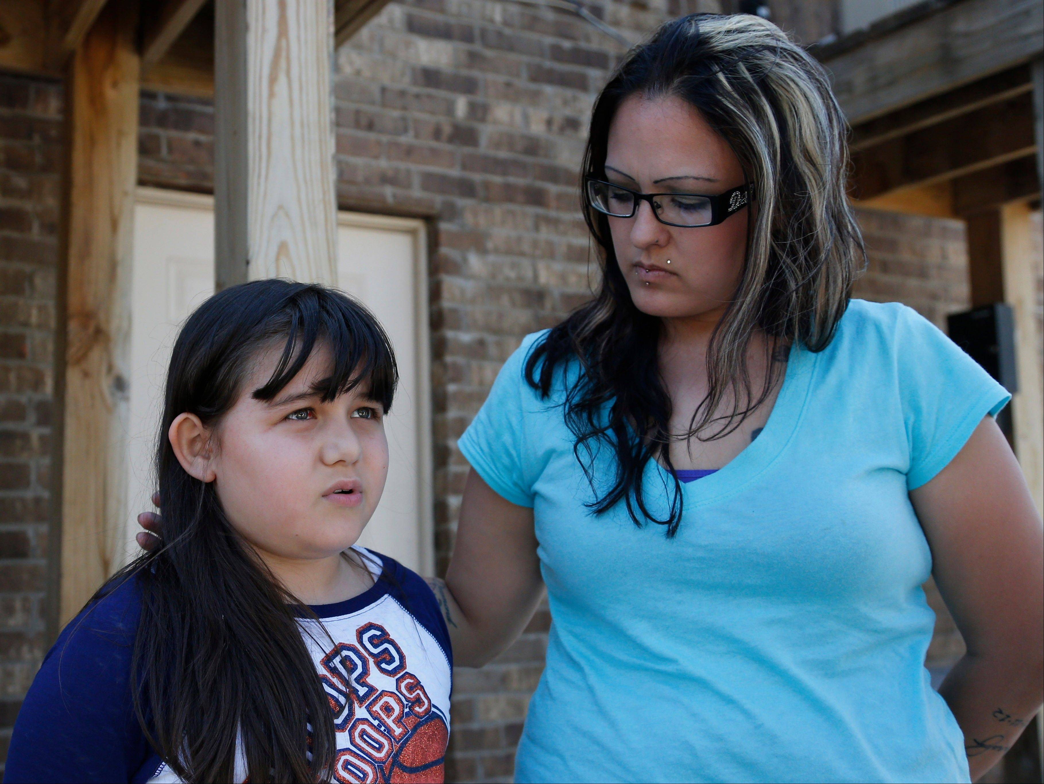 Jazmin Rodriguez, left, and her mother, LaTisha Garcia, right, looks on, in Moore, Okla., Thursday, May 23, 2013. Garcia carried her injured daughter away from a school that was hit by a tornado on Monday. The image of the moment has become one of the enduring images from the storm.