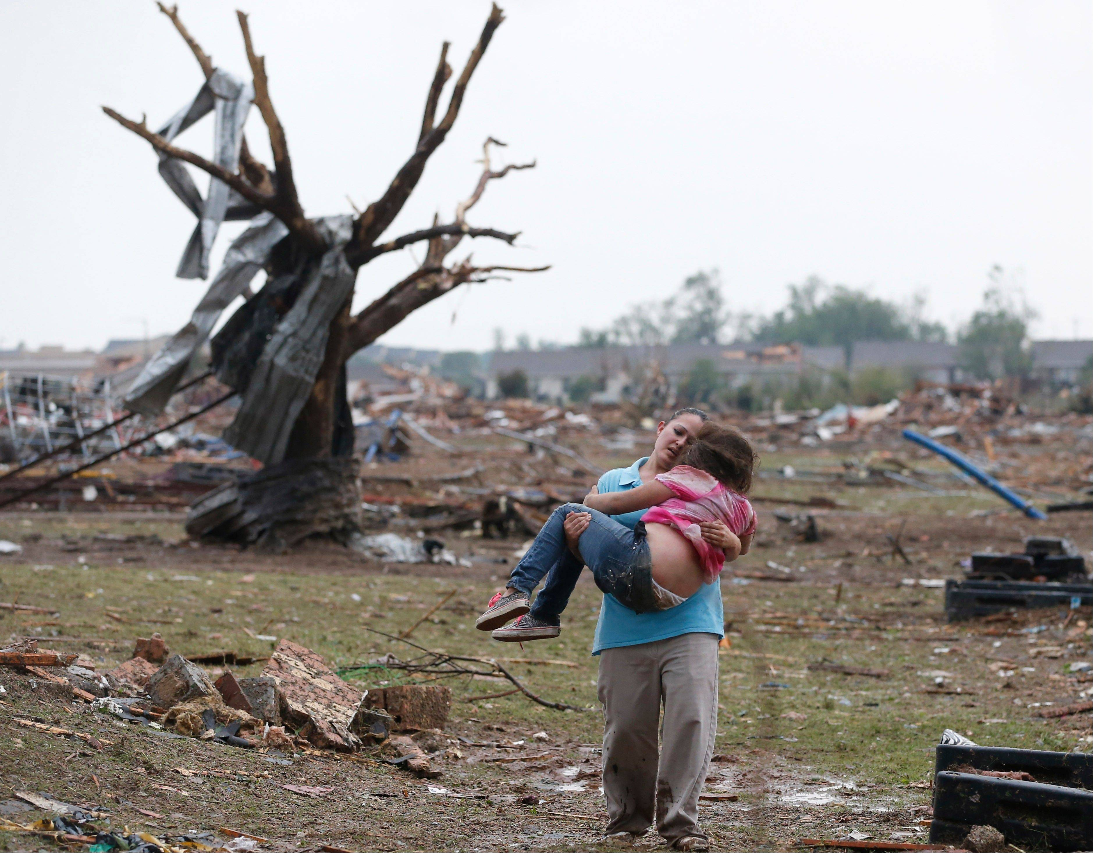 LaTisha Garcia carries her 8-year-old daughter, Jazmin Rodriguez near Plaza Towers Elementary School after a massive tornado carved its way through Moore, Okla., leaving little of the school and neighborhood. This picture, published on hundreds of front pages around the world, has become one of the enduring images from the storm.