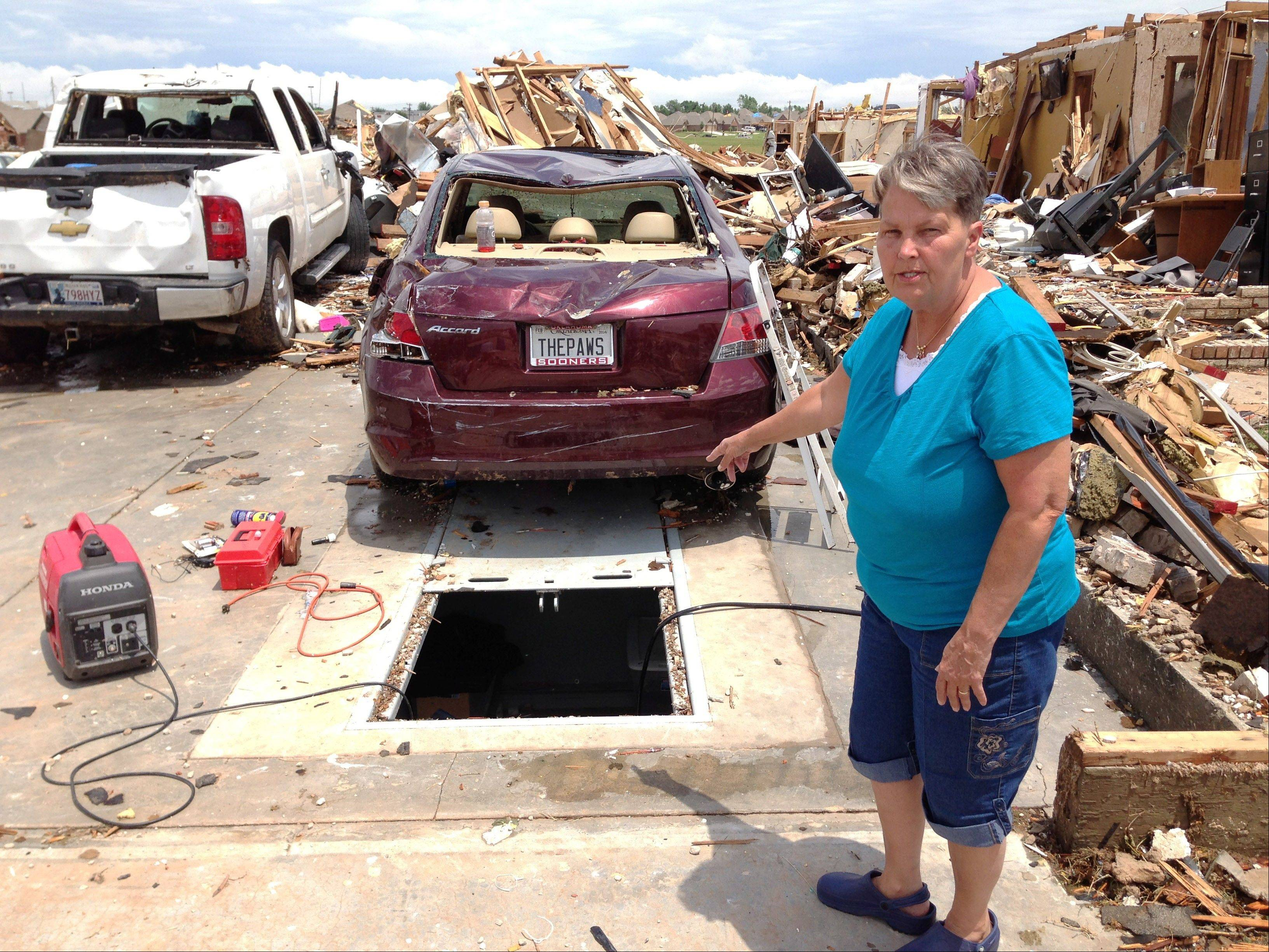 Sherry Wells stands near the storm shelter where she took cover when a tornado destroyed her home on Monday May 20, 2013 in Moore, Okla. Wells said she and her husband won a lottery draw to receive a government-subsidized rebate to install the storm shelter. A contractor finished work on the concrete bunker beneath the slab of their garage about three weeks before the tornado hit.