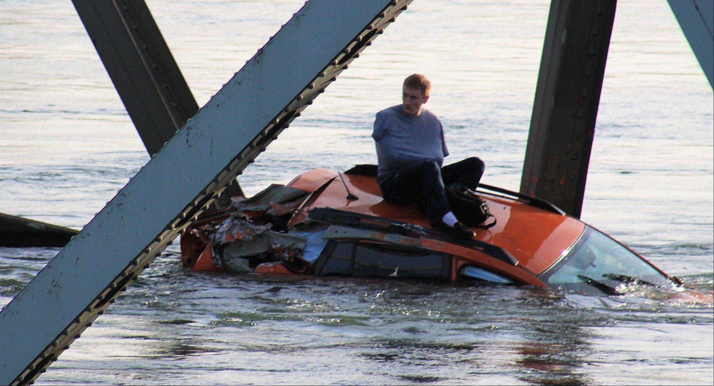 A man is seen sitting atop a car that fell into the Skagit River after the collapse of the Interstate 5 bridge there minutes earlier Thursday, May 23, 2013, in Mount Vernon, Wash.