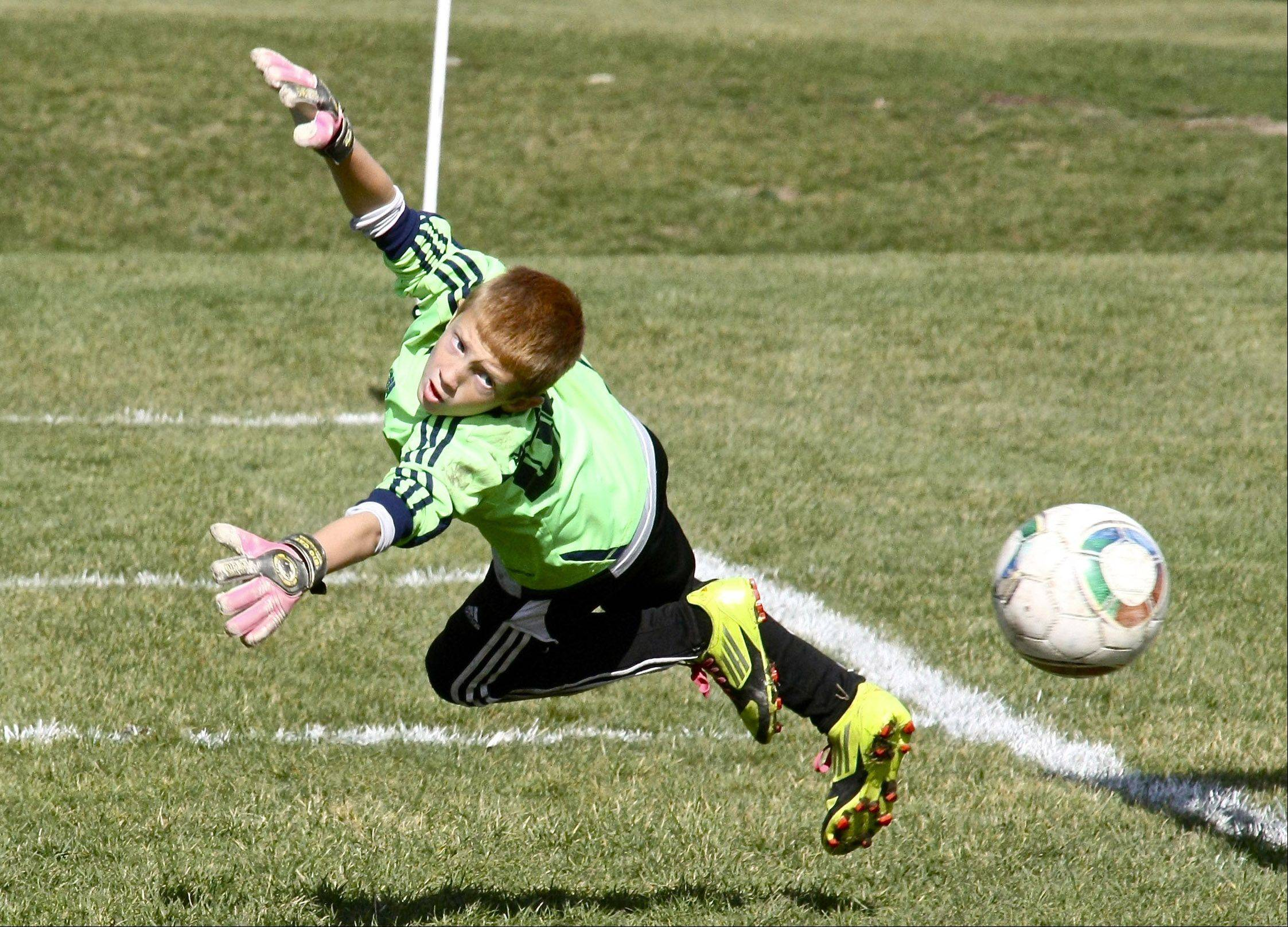 Nine-year-old Trevor Share defies gravity deflecting a soccer ball during a game with the Kickers Soccer League in Elgin.