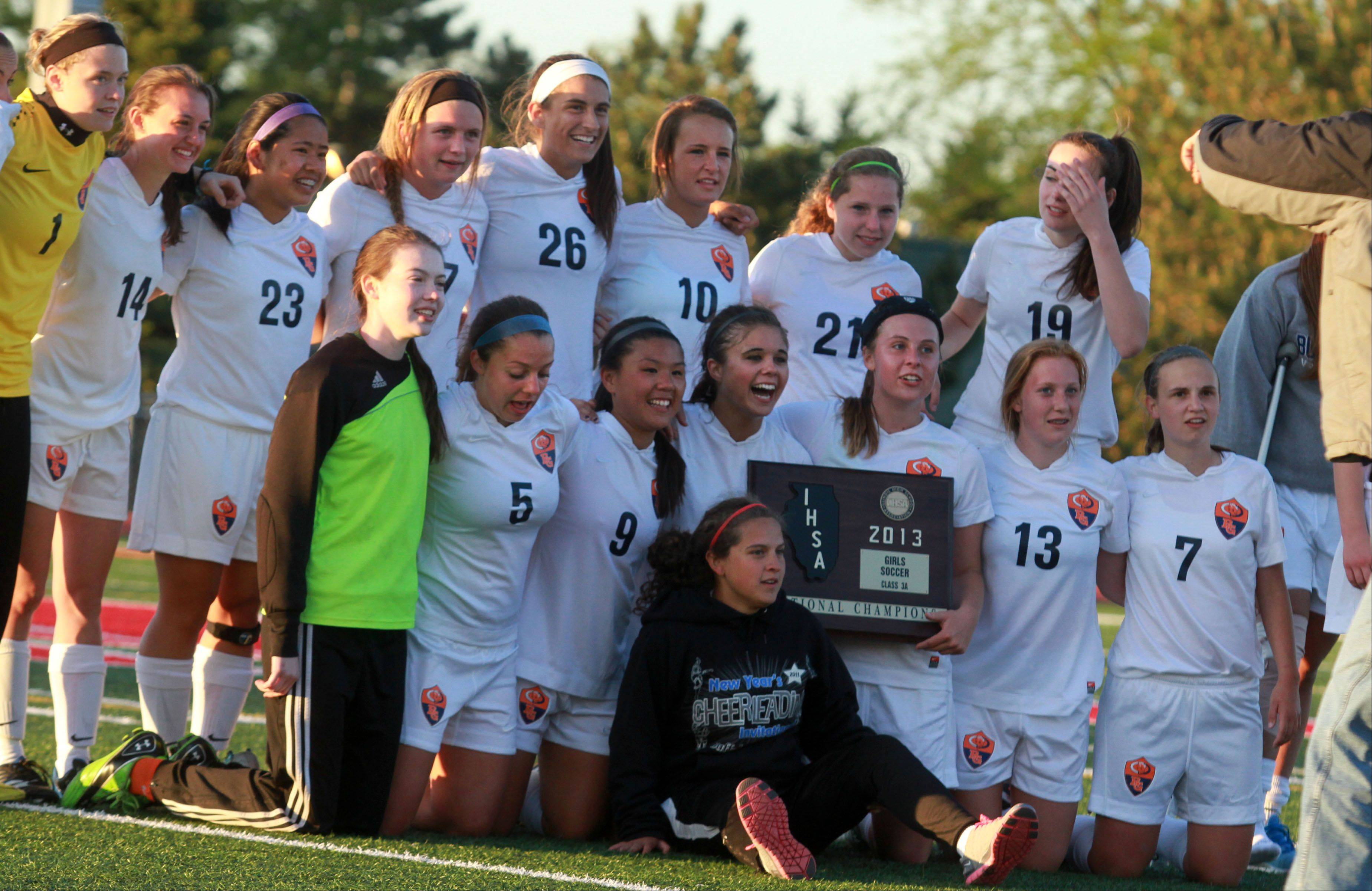 Buffalo Grove, with the Class 3A Mundelein girls soccer sectional plaque, poses for photos for parents after winning the sectional final matchup with Hersey on Friday.