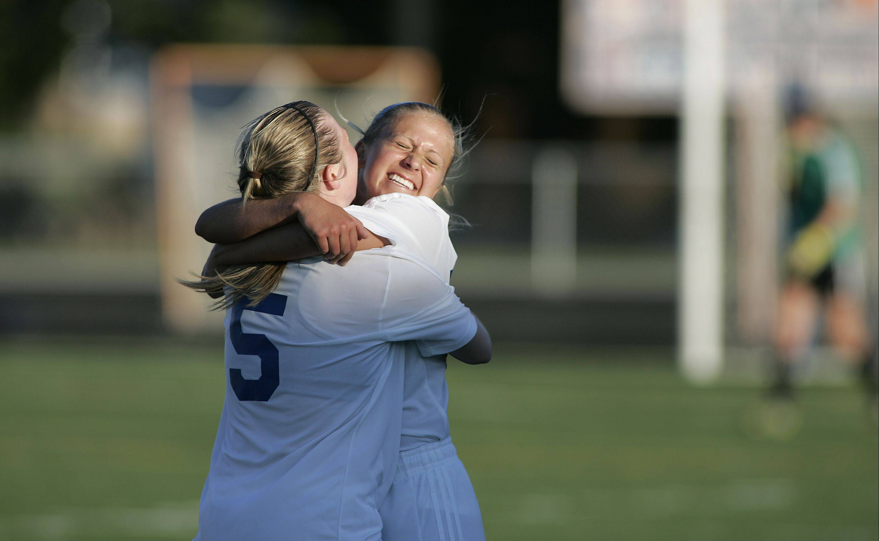 St. Charles North's Natalie Winkates (5) hugs her teammate Kelly Manski (17) after their win over Geneva Friday for the Class 3A Hoffman Estates sectional championship.