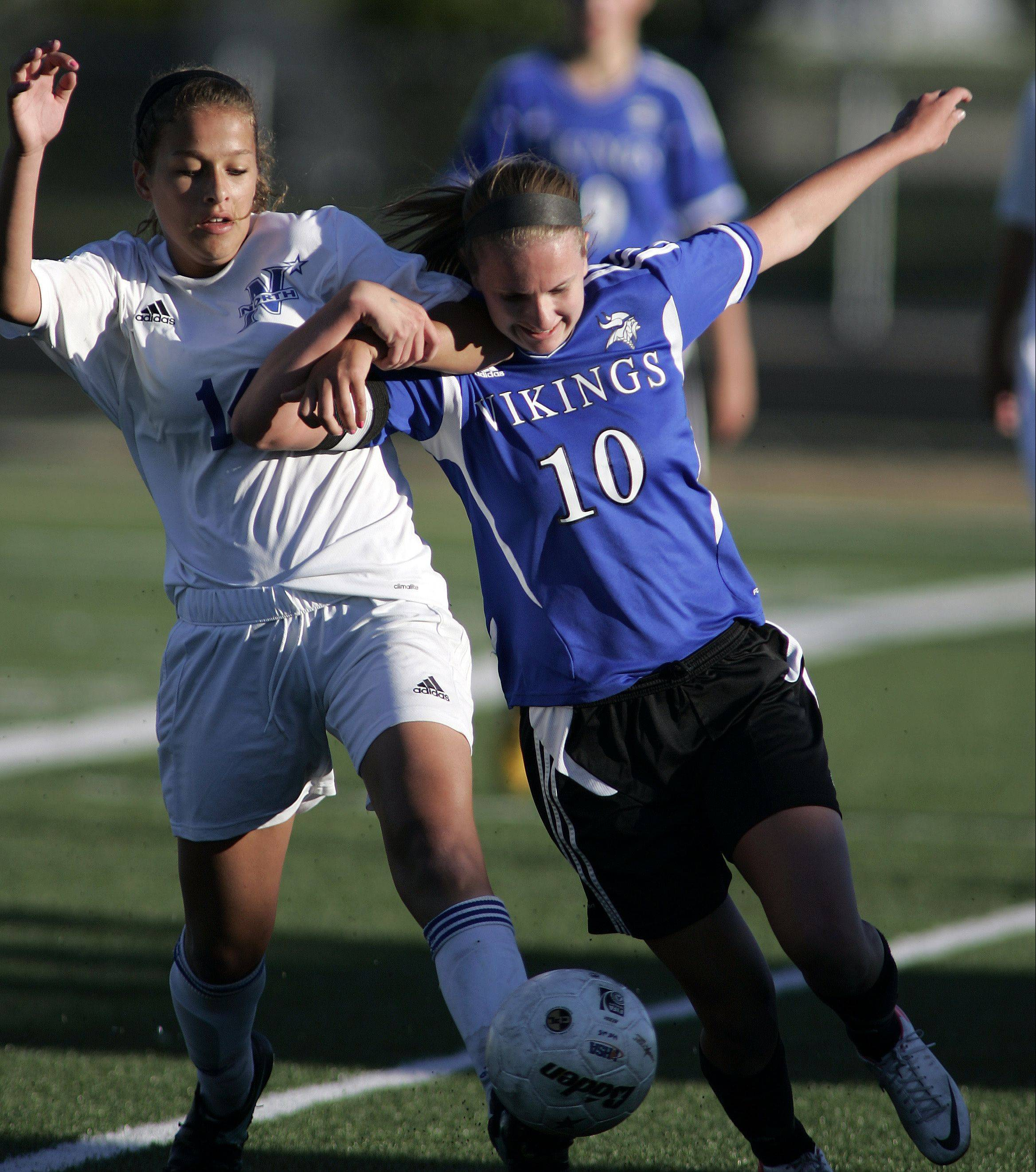 St. Charles North's Elizabeth Parrilli (14) battles Geneva forward Amanda Lulek (10) for control of the ball Friday.