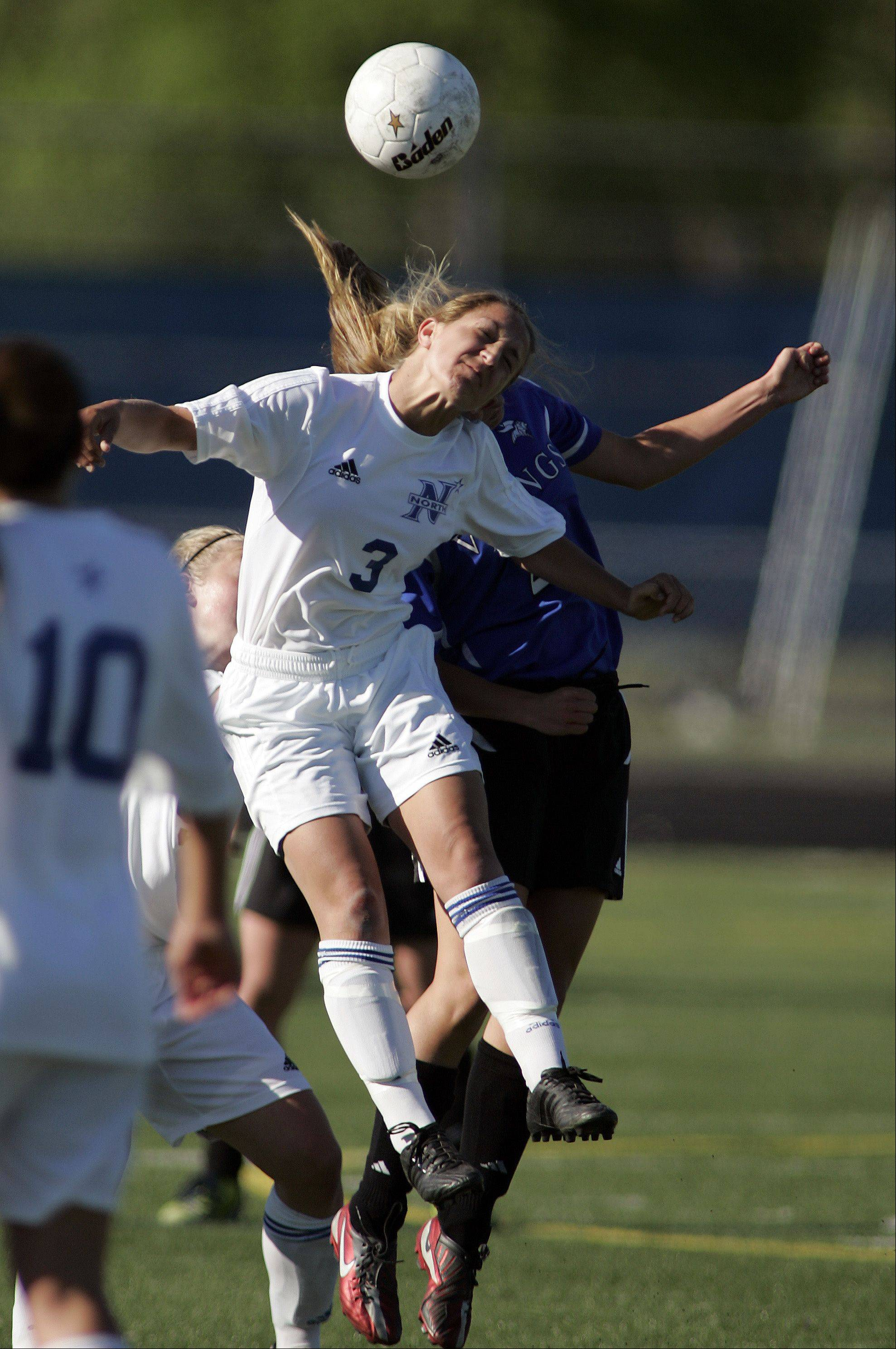 St. Charles North's Alex Gage (3) goes head to head with Geneva forward Mary Landry (21) during the IHSA Girl's 3A Sectional Soccer Tournament Friday at Hoffman Estates High School.