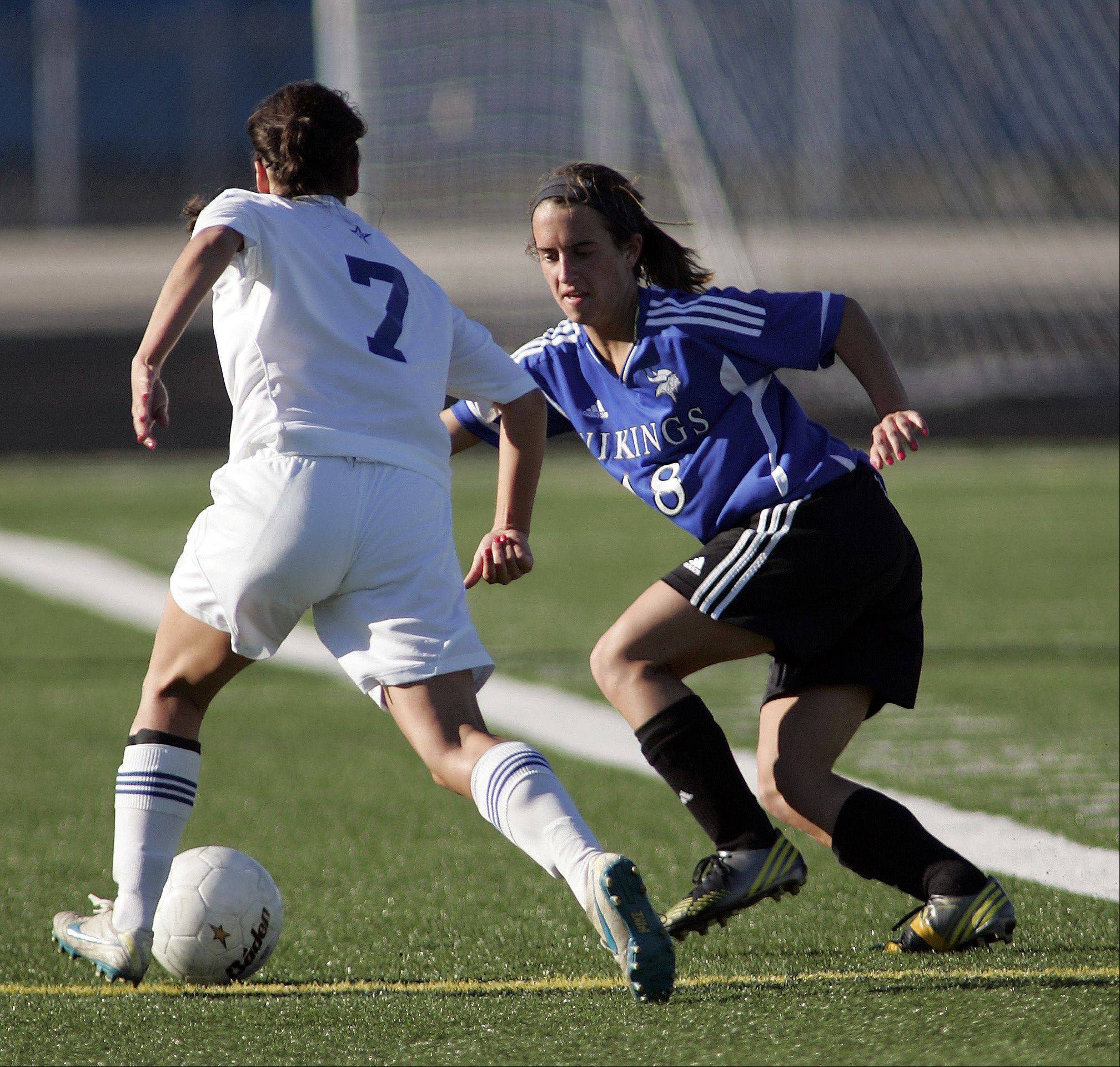 St. Charles North's Ashlyn Walter (7) works around Geneva defender Molly Stanfa (18) during the IHSA Girl's 3A Sectional Soccer Tournament Friday at Hoffman Estates High School.