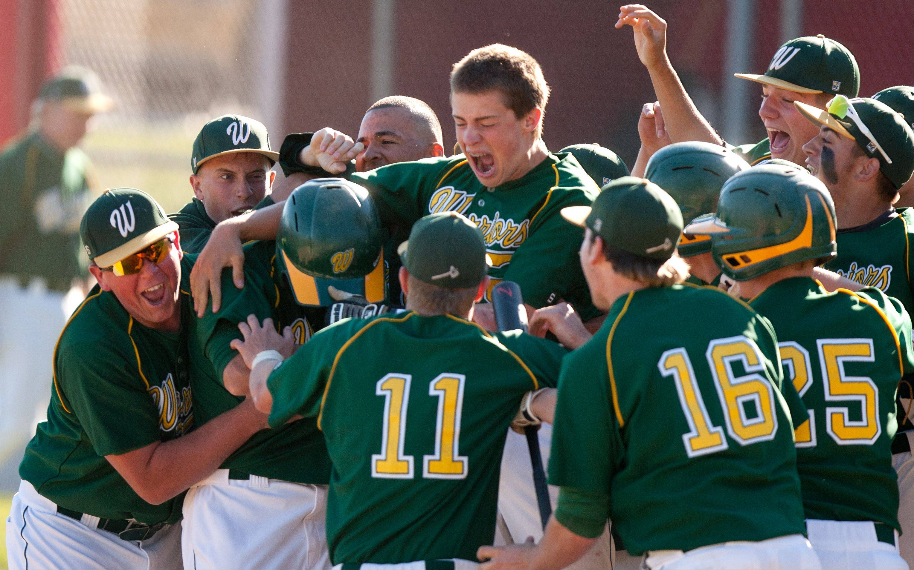 Waubonsie Valley's Tyler Hasper, left, is mobbed by teammates after hitting a walk-off home run for a 2-0 win against Hinsdale Central, during the Hinsdale Central Baseball Regional.