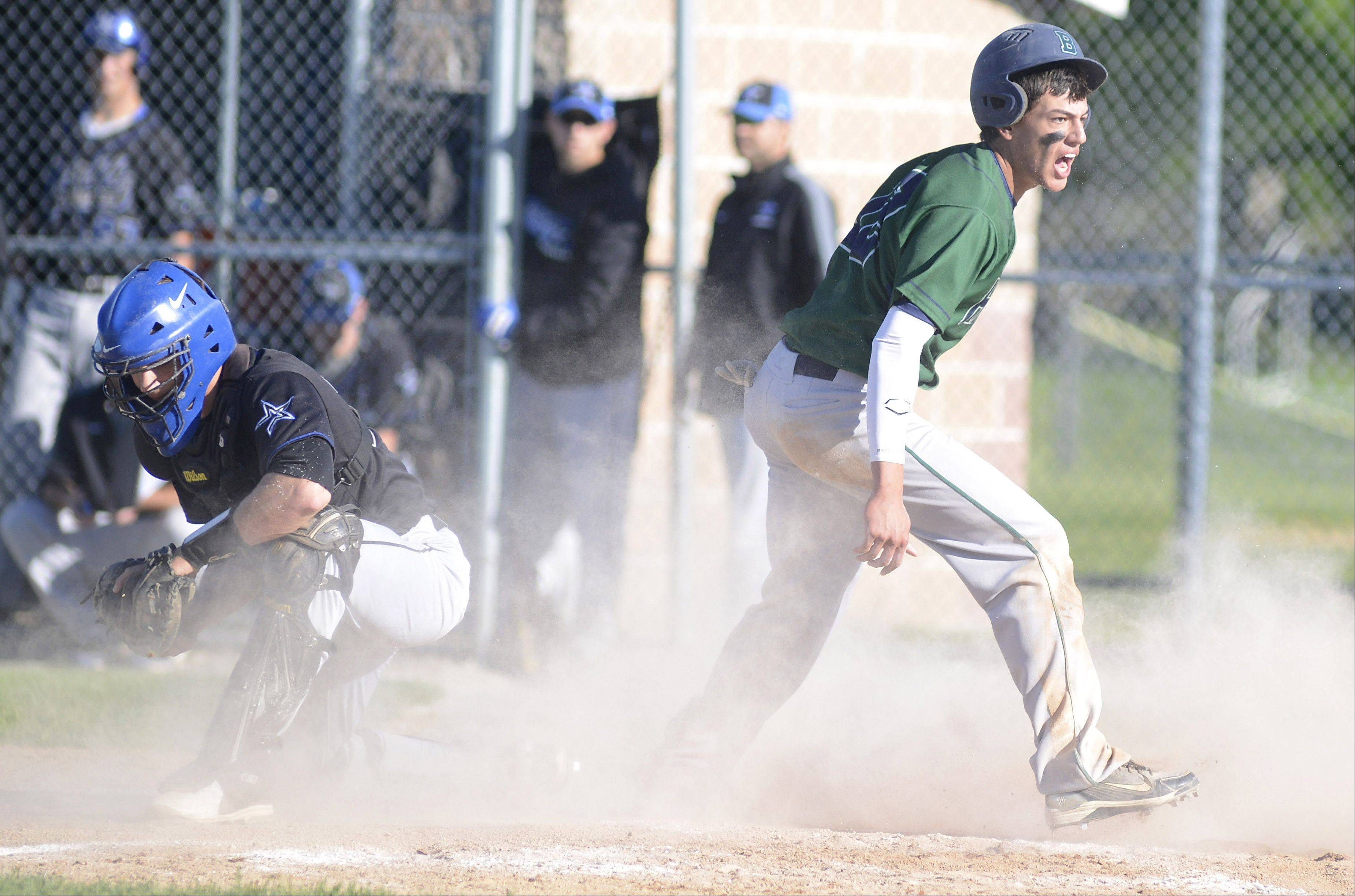 Bartlett's Jake Barrutia leaps up from a safe slide into home plate and celebrates leaving St. Charles North's catcher Ryan Thomas behind in the fifth inning of the Class 4A regional game on Friday.