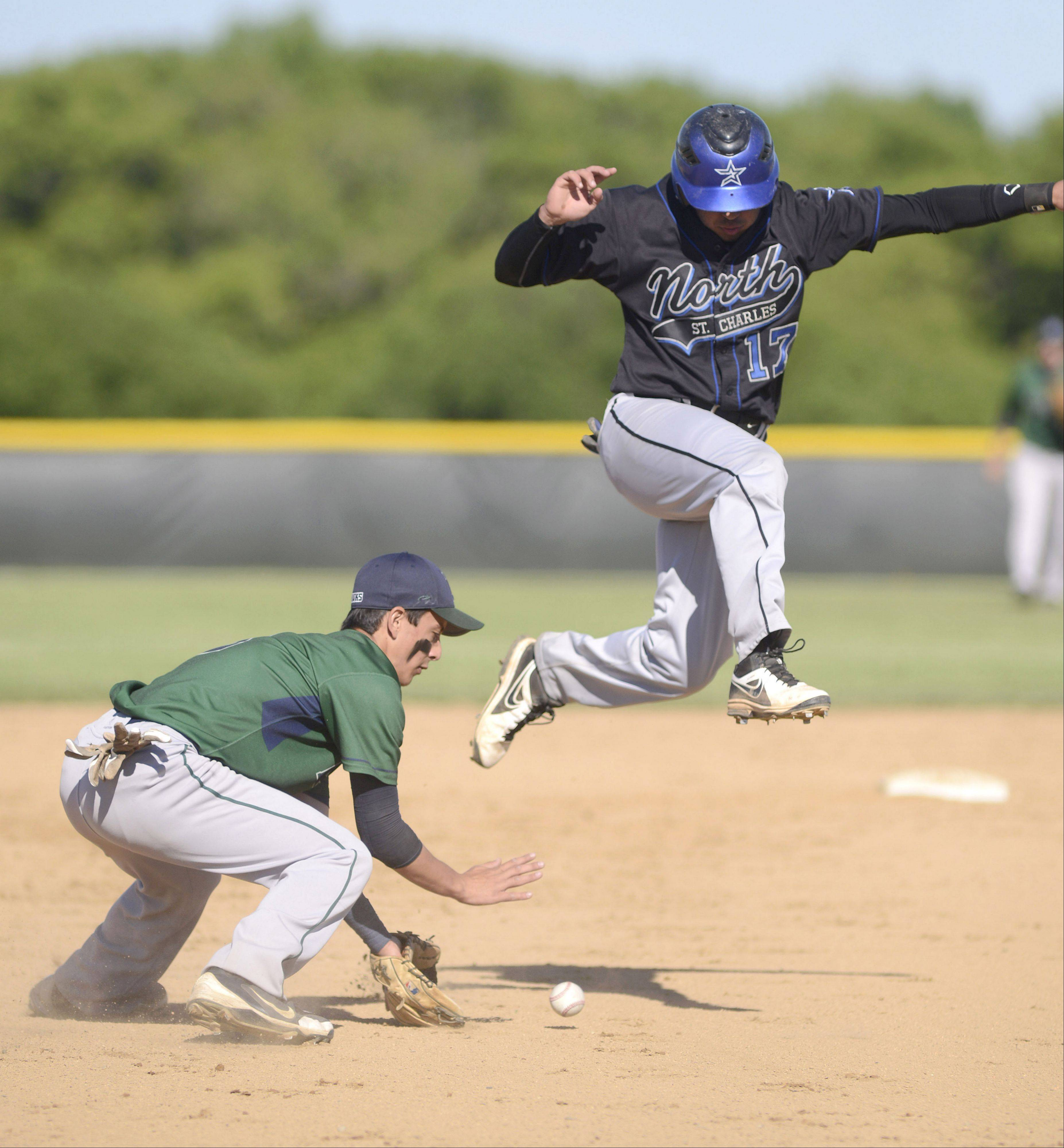 Bartlett's Matt Vitulli scoops up the ball to throw to first as St. Charles North's Frankie Farry leaps to avoid a collision on the way to third base Friday.