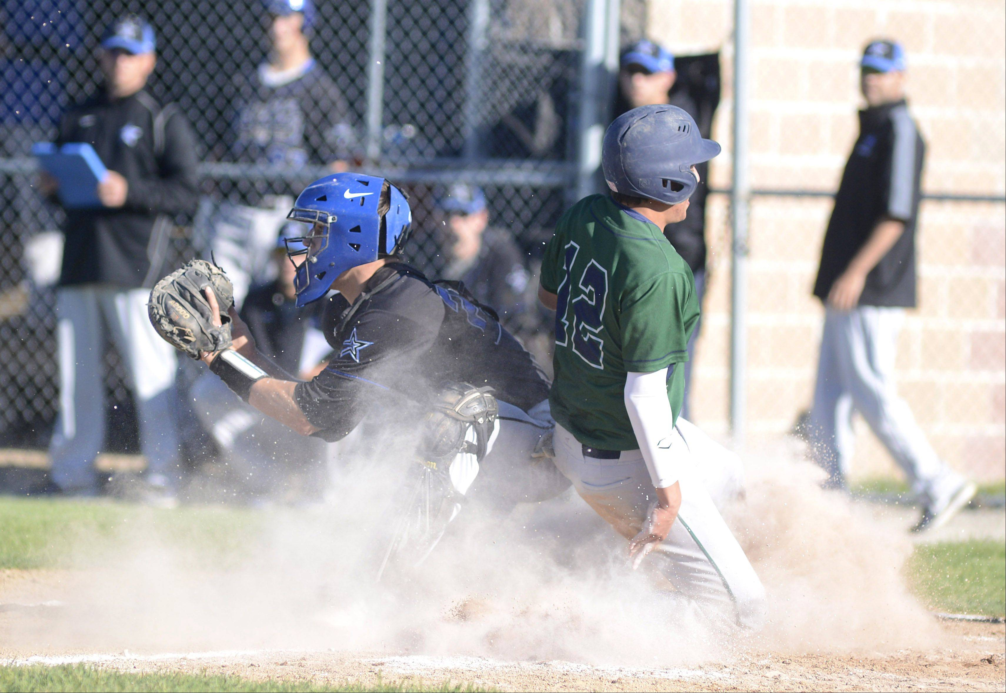 Bartlett's Jake Barrutia slides into home plate safely behind St. Charles North catcher Ryan Thomas in the fifth inning Friday.