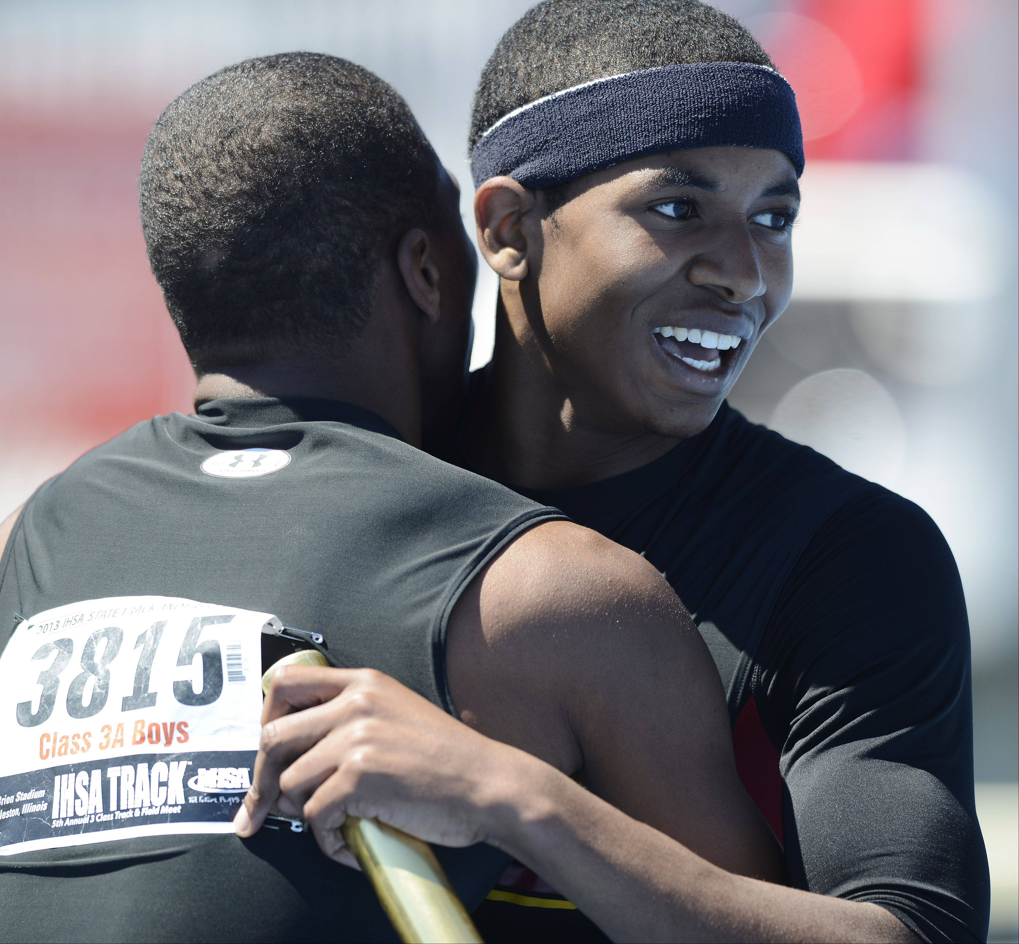 Schaumburg's Juwaan Richard, right, is congratulated at the finish line by teammate Stacey Smith in the Class 3A 4x200-meter relay during the boys state track preliminaries in Charleston Friday.