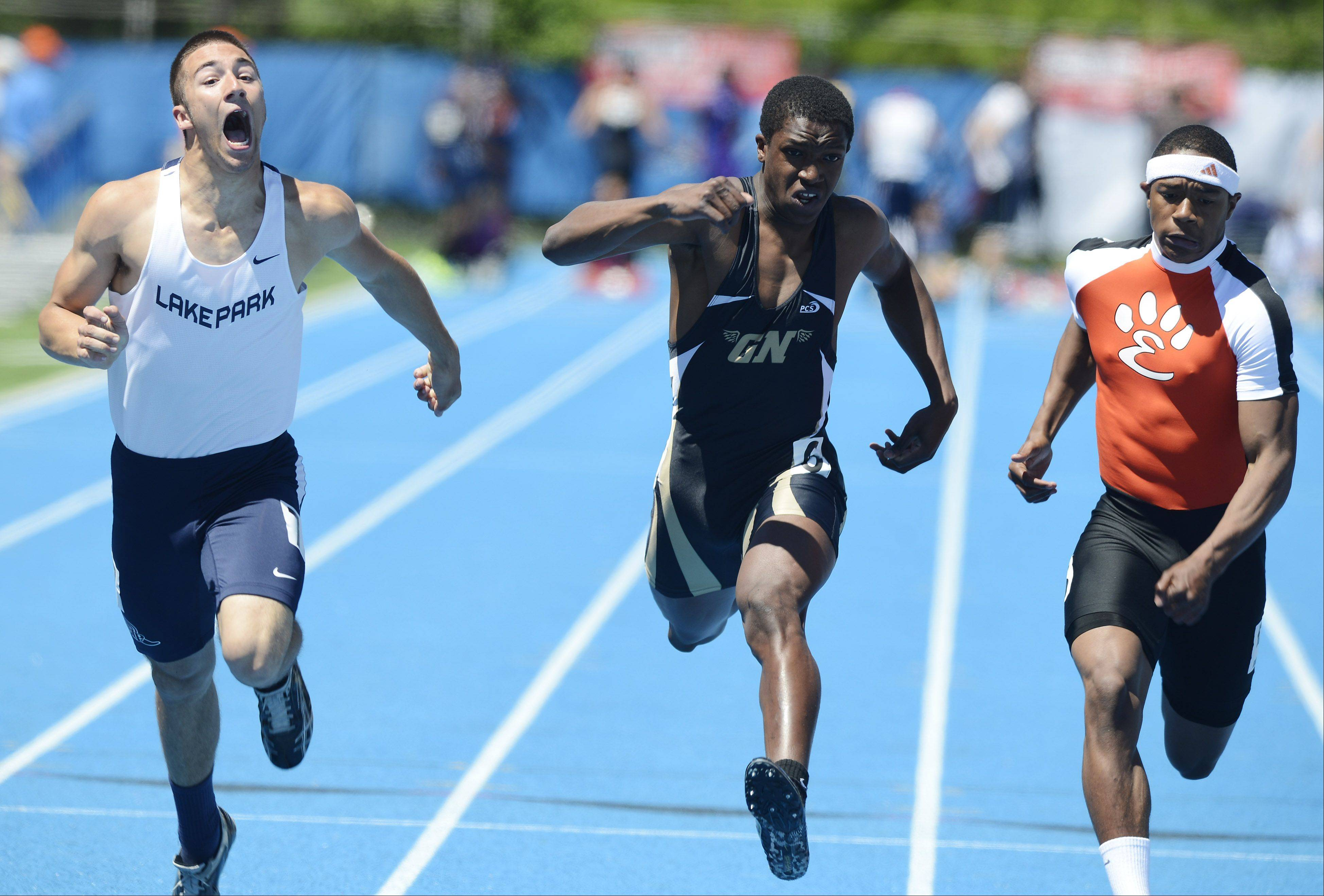 Lake Park's Scott Filip lets out a yell at the finish line while running the 100-meter dash alongside Grayslake North's Titus Booker, left, and Edwardsville's Craig James during the boys Class 3A state track preliminaries in Charleston Friday.