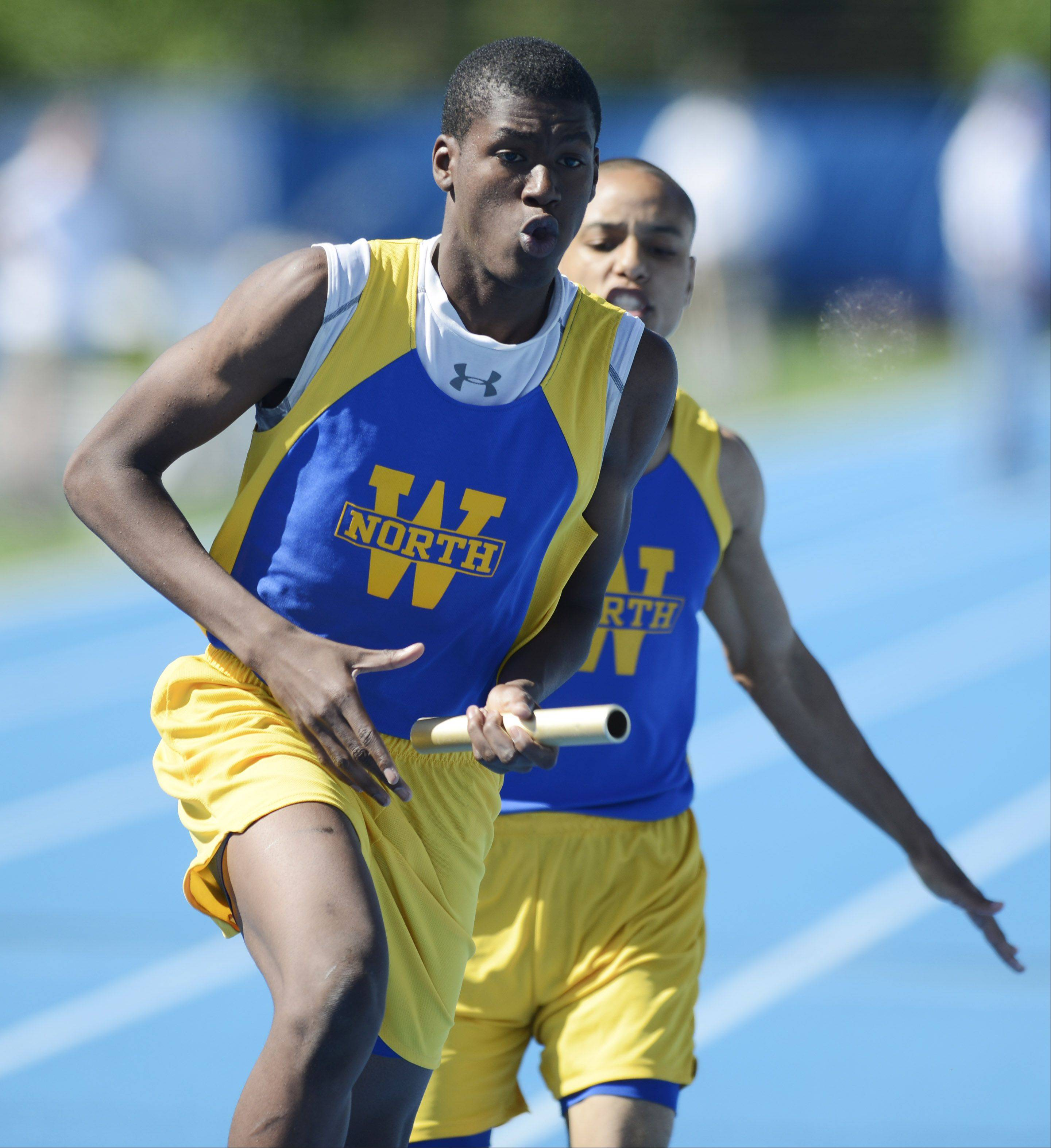 Wheaton North's Steven Connor, front, takes the baton from teammate Nehemiah Heckler in the Class 3A 4x400-meter relay during the boys state track preliminaries in Charleston Friday.
