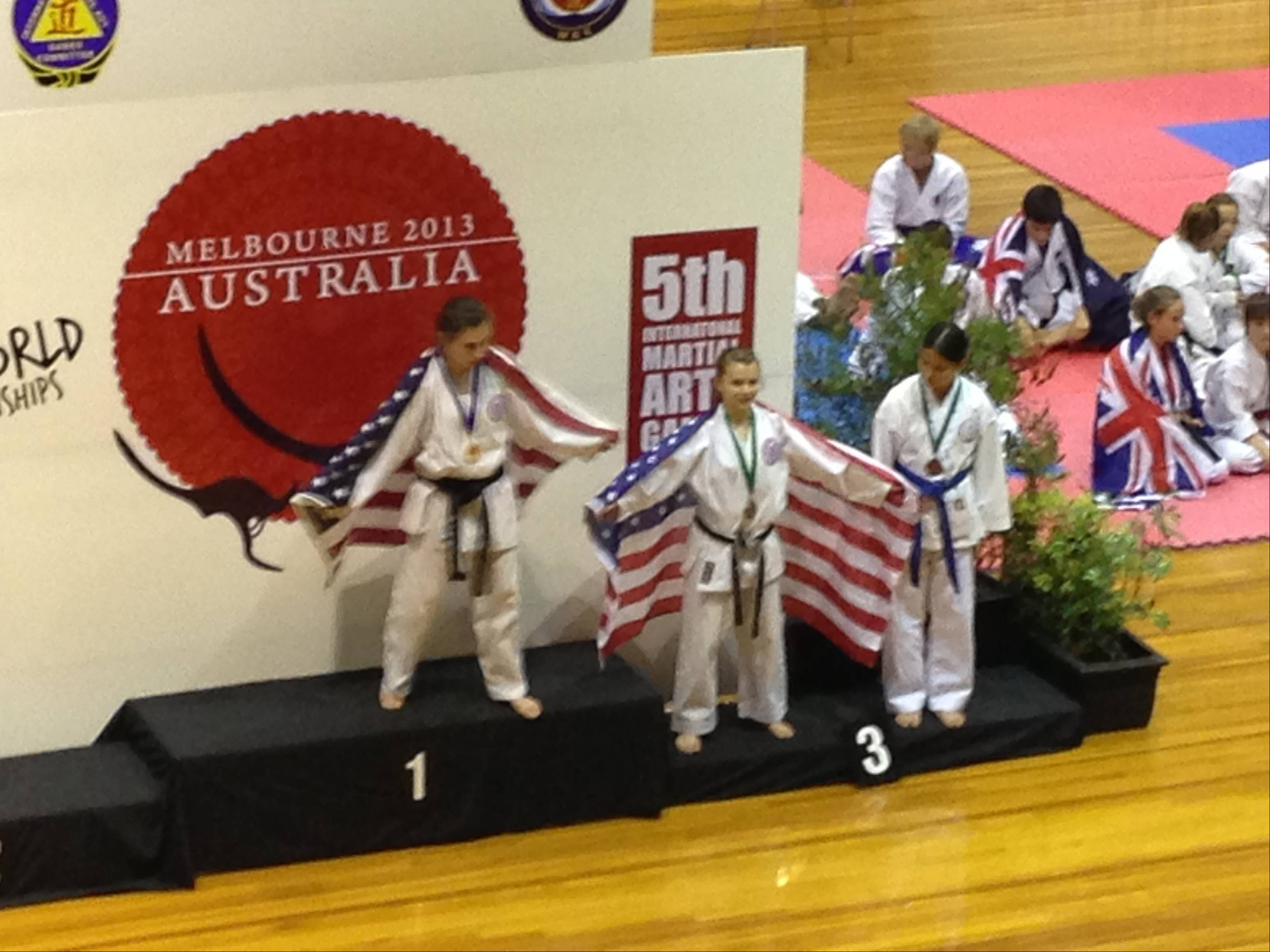 Rebecca Fishman stands on the gold-medal platform draped in the United States flag after winning the 13-year-old lightweight world championship in kumite (fighting).