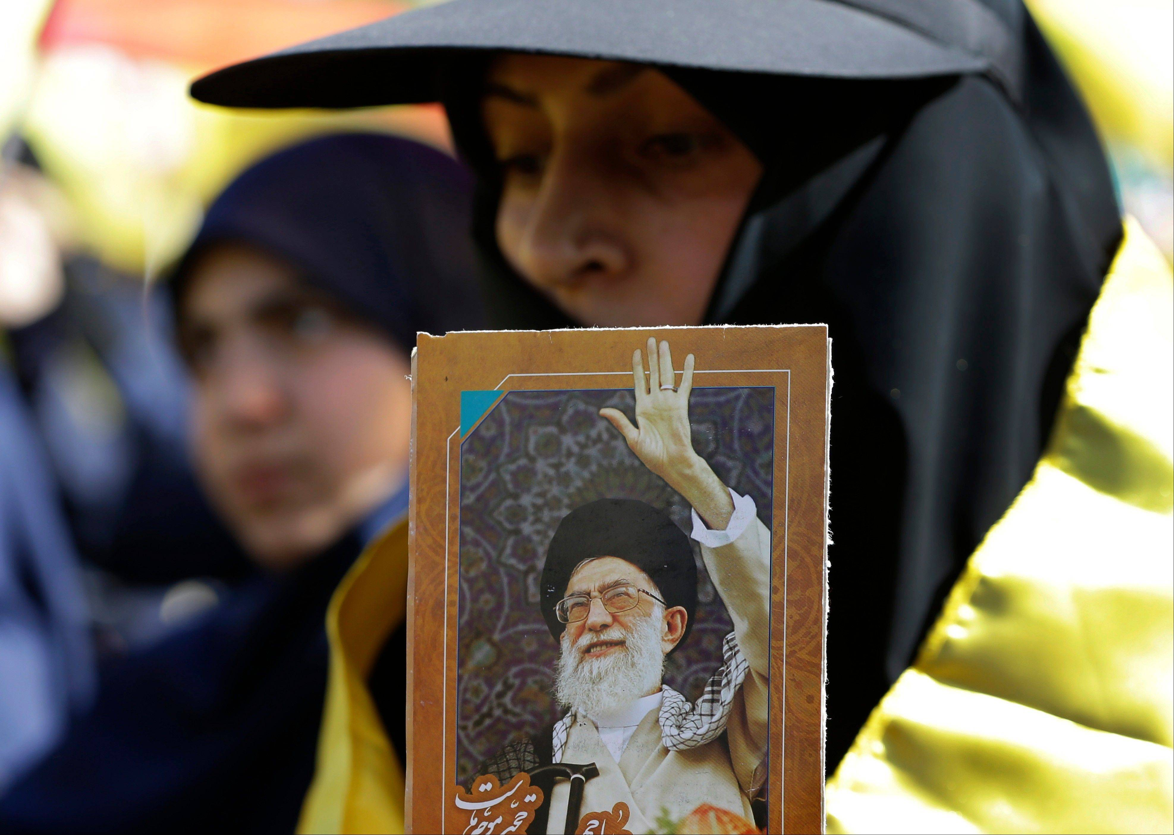 A Hezbollah supporter holds a portrait of the Iranian Supreme Leader Ayatollah Ali Khamenei, as she listens Saturday to the speech of Hezbollah leader Sheik Hassan Nasrallah, broadcast during a rally commemorating �Liberation Day,� which marks the withdrawal of the Israeli army from southern Lebanon in 2000, in Mashghara village, Bekaa valley, Lebanon.