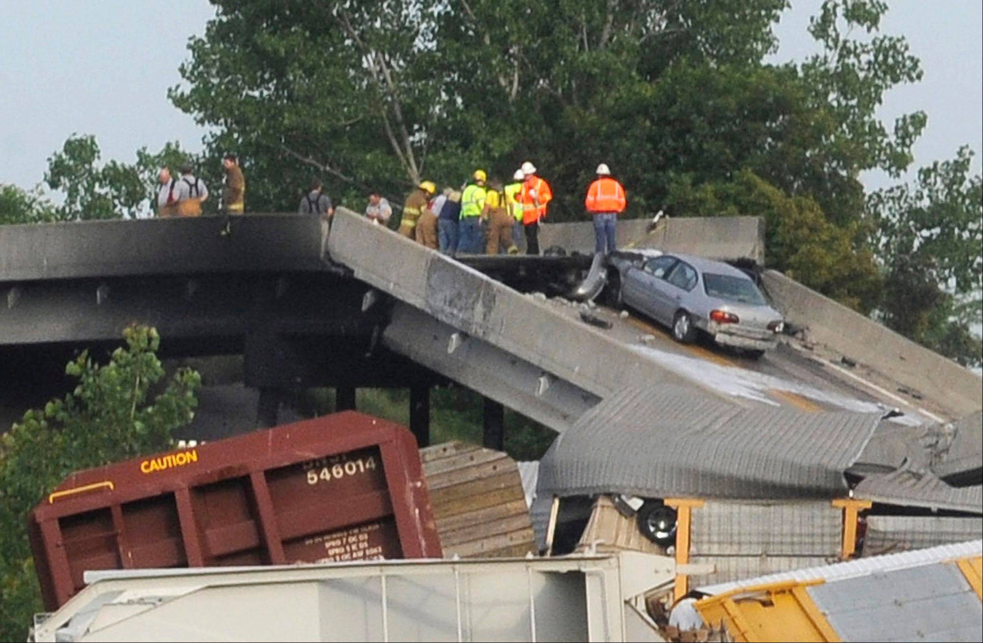 Emergency personnel take control Saturday at the scene of a train derailment near Rockview, Mo. The National Transportation Safety Board has launched an investigation into the cause of the cargo train collision that partially collapsed a highway overpass.