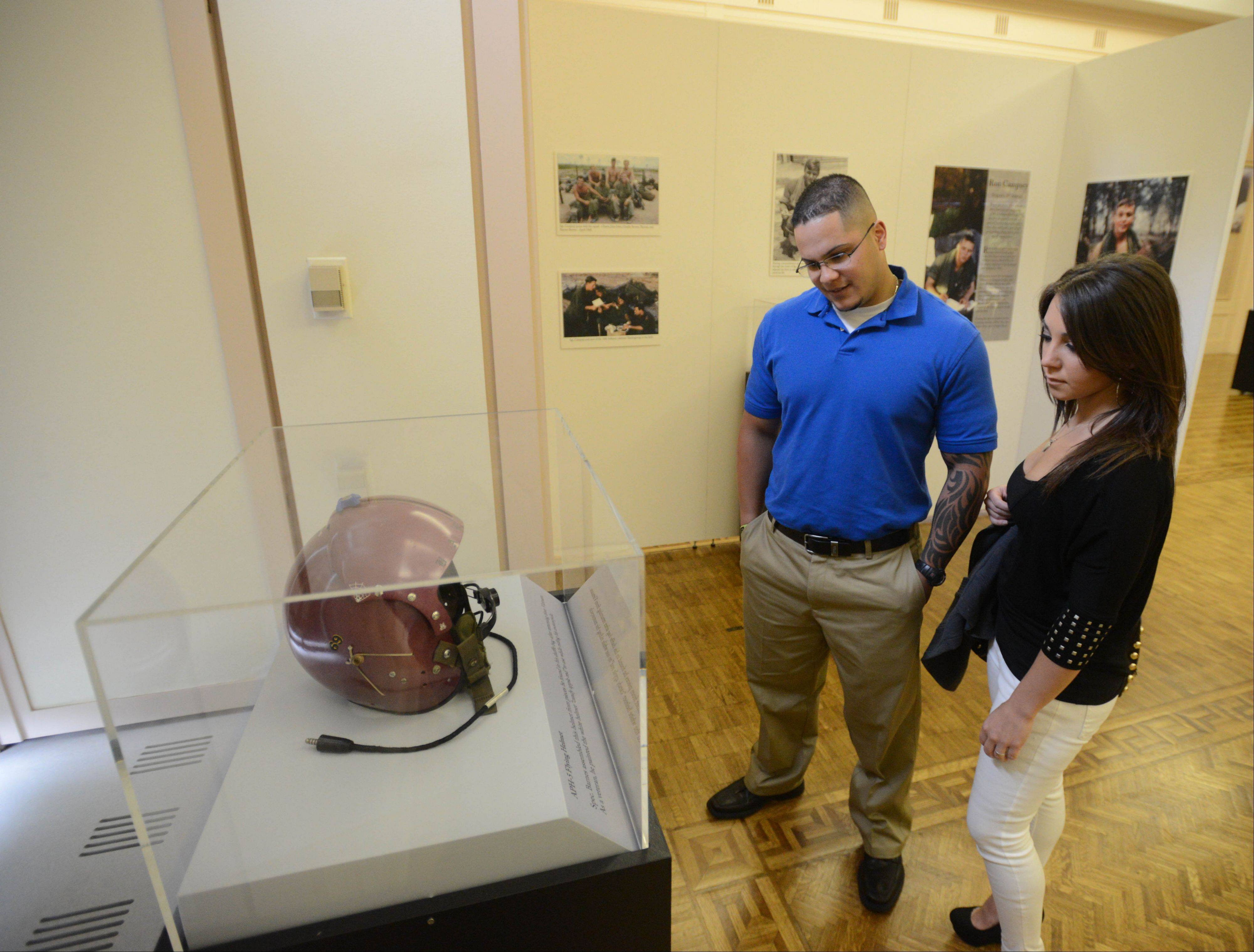David Roldan of Chicago and Francesca LeDoux of Broadview view the �Faces of the 1st,� exhibit, which opened Saturday at the First Division Museum at Cantigny Park in Wheaton. The exhibit tells the story of the Army�s 1st Infantry Division from World War I to modern conflicts through the eyes of 17 veterans.