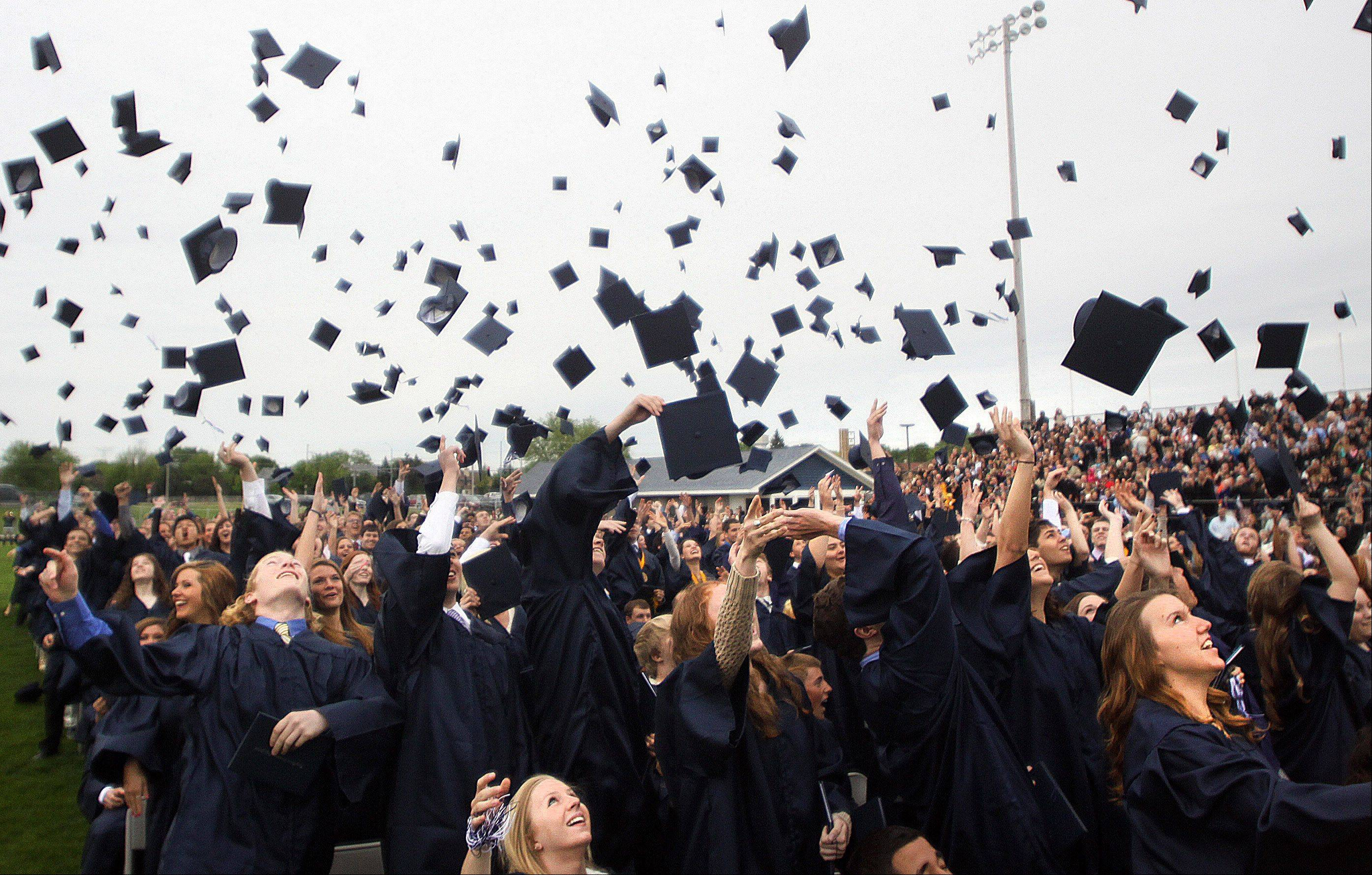 Members of the class of 2013 toss their caps at the conclusion of Cary-Grove High School commencement exercises at Al Bohrer Athletic Field on the Campus of Cary-Grove High School on Saturday morning.