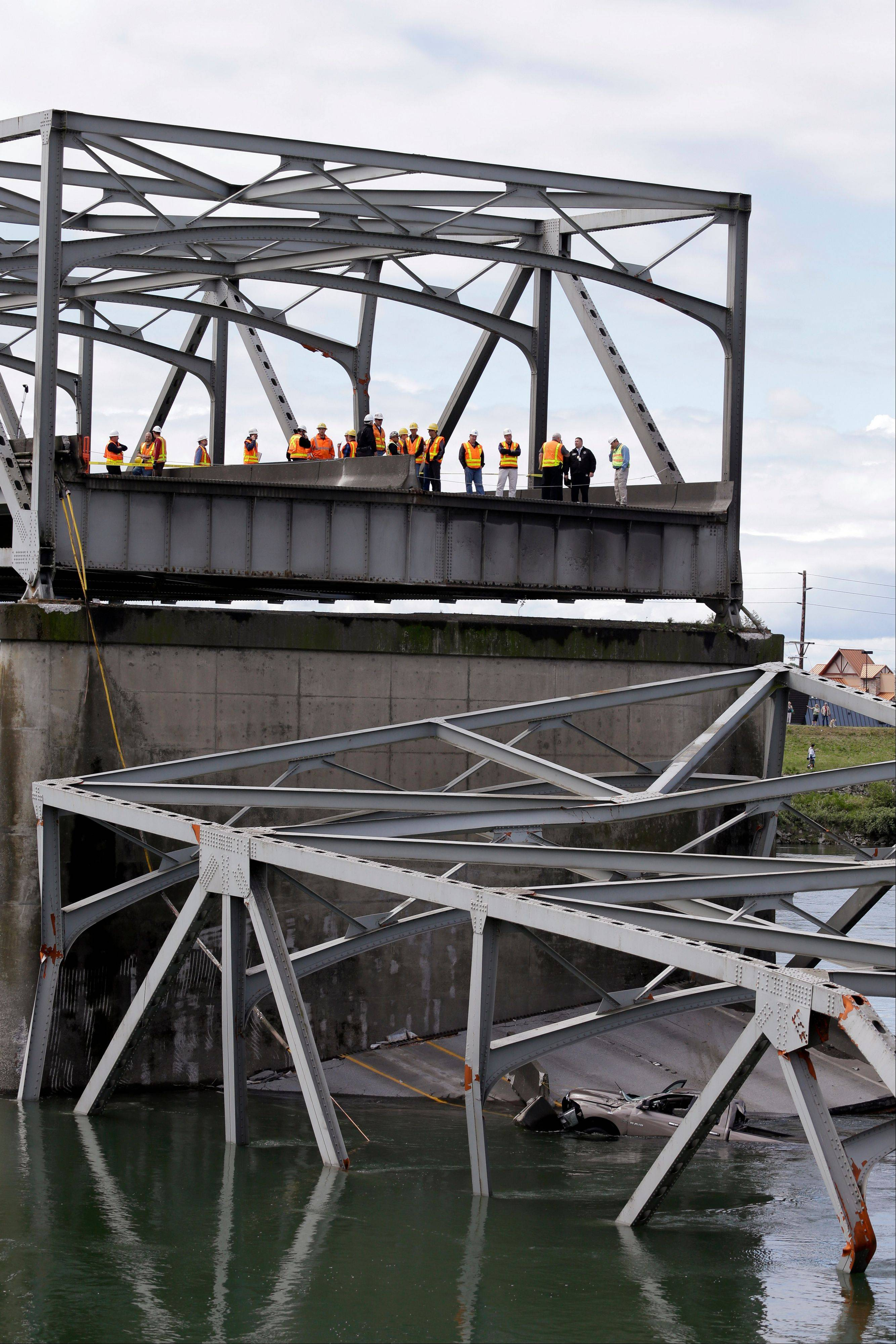 Workers look over a collapsed portion of the Interstate 5 bridge Friday at the Skagit River where a pickup truck can be seen in the water below. There is wide recognition at all levels of government that the failure to address aging infrastructure will likely undermine safety and hinder economic growth. But there is no consensus on how to pay for improvements.