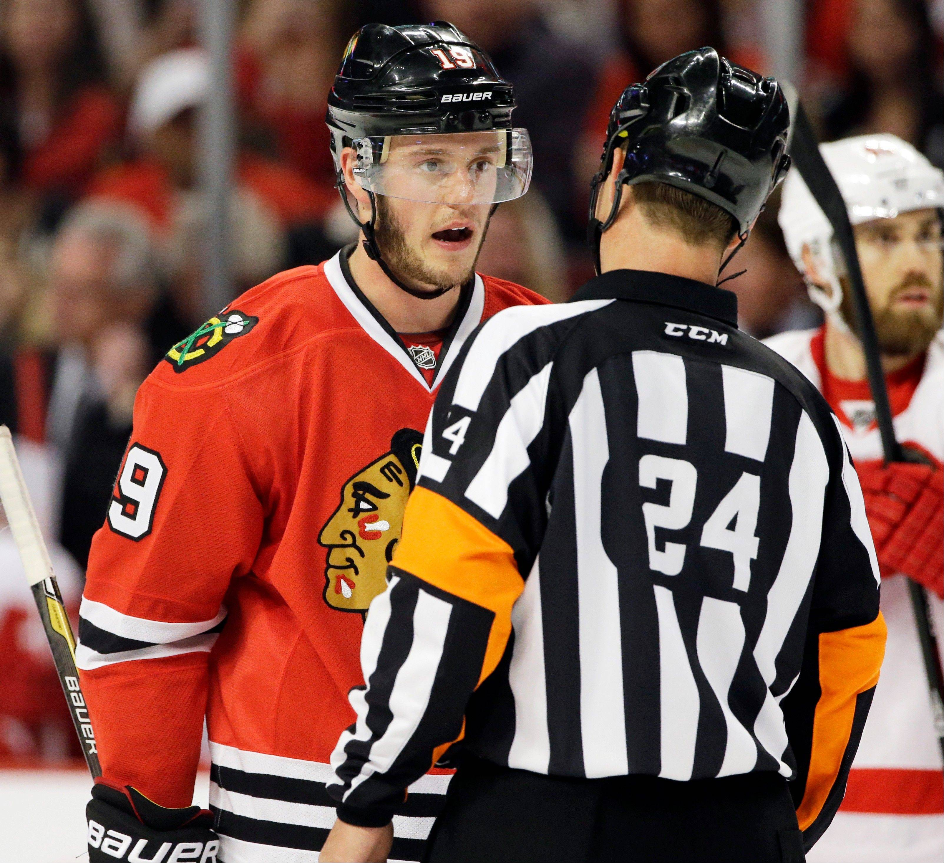 Jonathan Toews, left, talks with referee Stephen Walkom during the second period of Game 5 of the NHL hockey Stanley Cup playoffs Western Conference semifinals against the Detroit Red Wings in Chicago, Saturday, May 25, 2013.