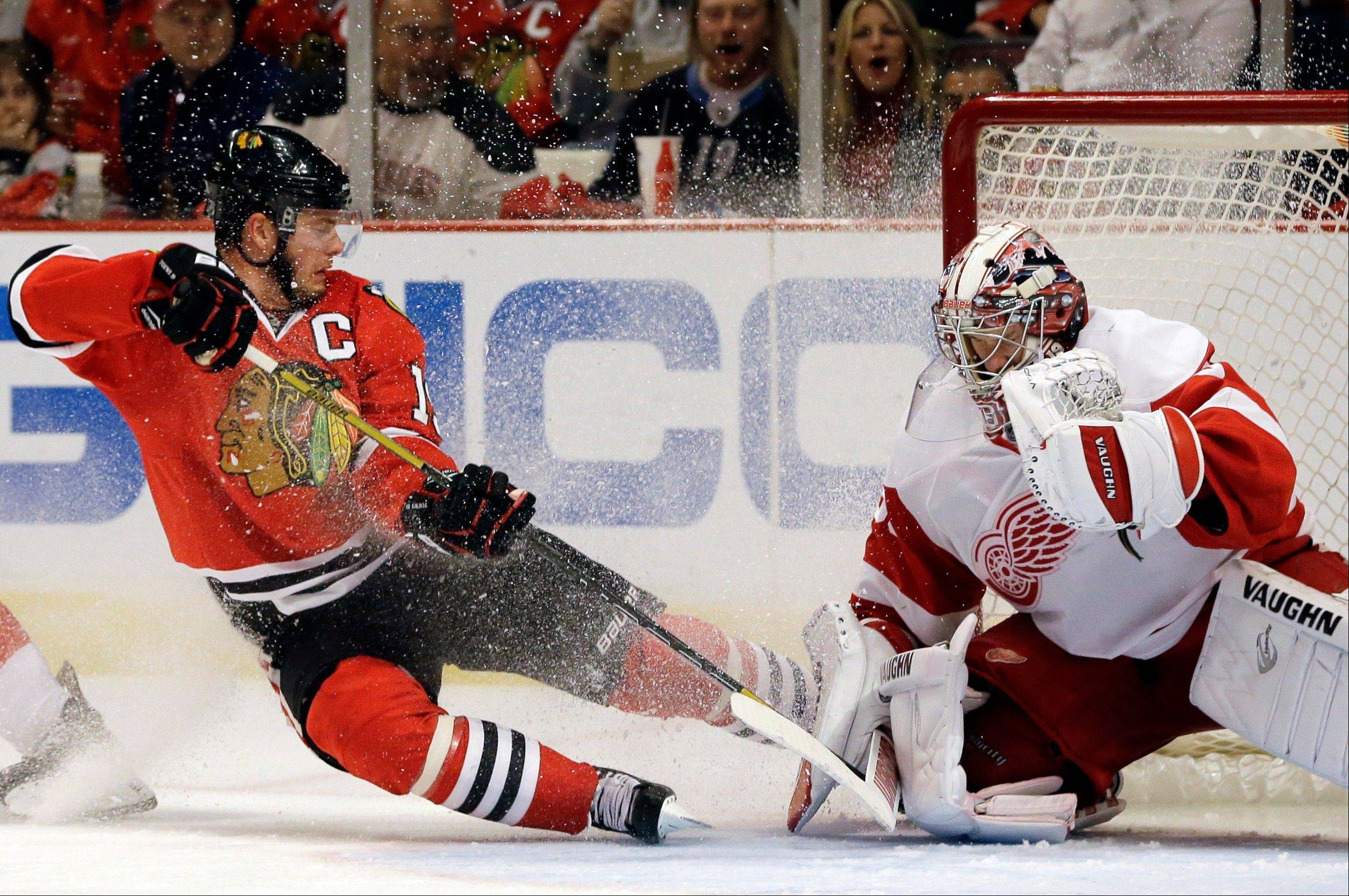 Detroit Red Wings goalie Jimmy Howard, right, saves a shot by Chicago Blackhawks� Jonathan Toews, left, during the second period of Game 5 of the NHL hockey Stanley Cup playoffs Western Conference semifinals in Chicago, Saturday, May 25, 2013. (AP Photo/Nam Y. Huh)
