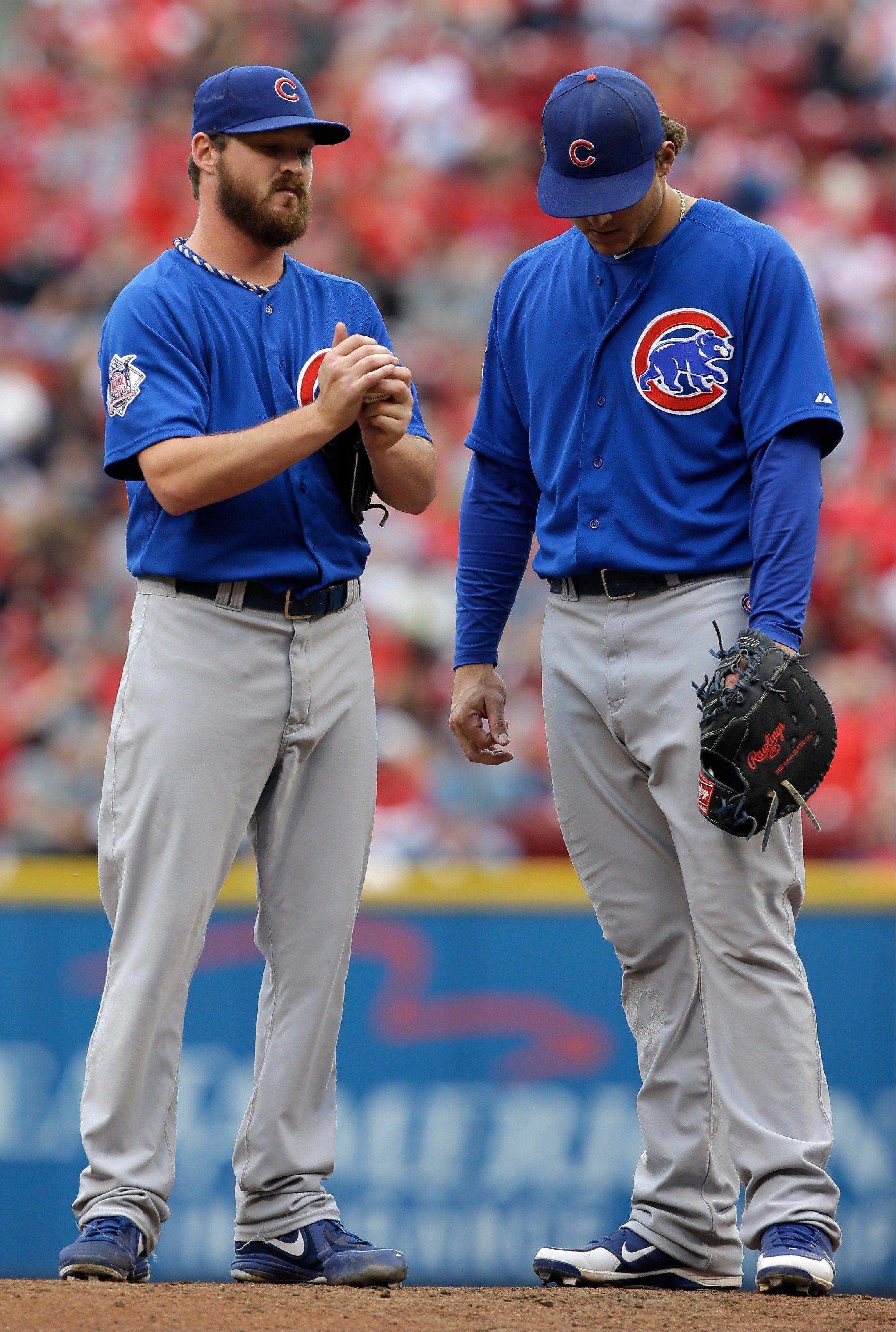 Chicago Cubs starting pitcher Travis Wood, left, stands with first baseman Anthony Rizzo on the mound in the fourth inning of a baseball game against the Cincinnati Reds, Saturday, May 25, 2013, in Cincinnati. (AP Photo/Al Behrman)