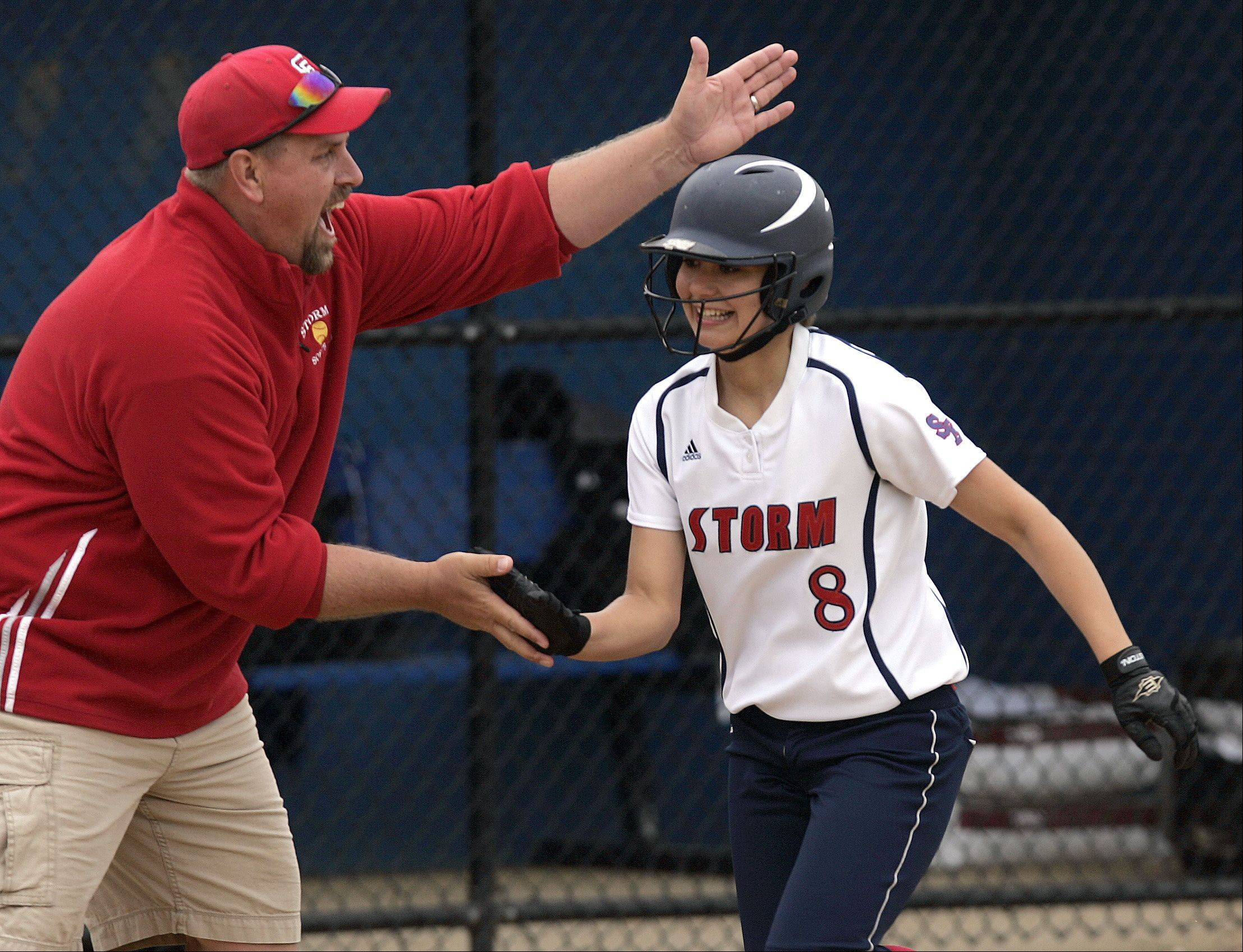 South Elgin�s Victoria Watt is greeted by head coach Jason Schaal at third base after belting a home run as the first batter in the game during the Class 4A regional softball final at St. Charles North Saturday.