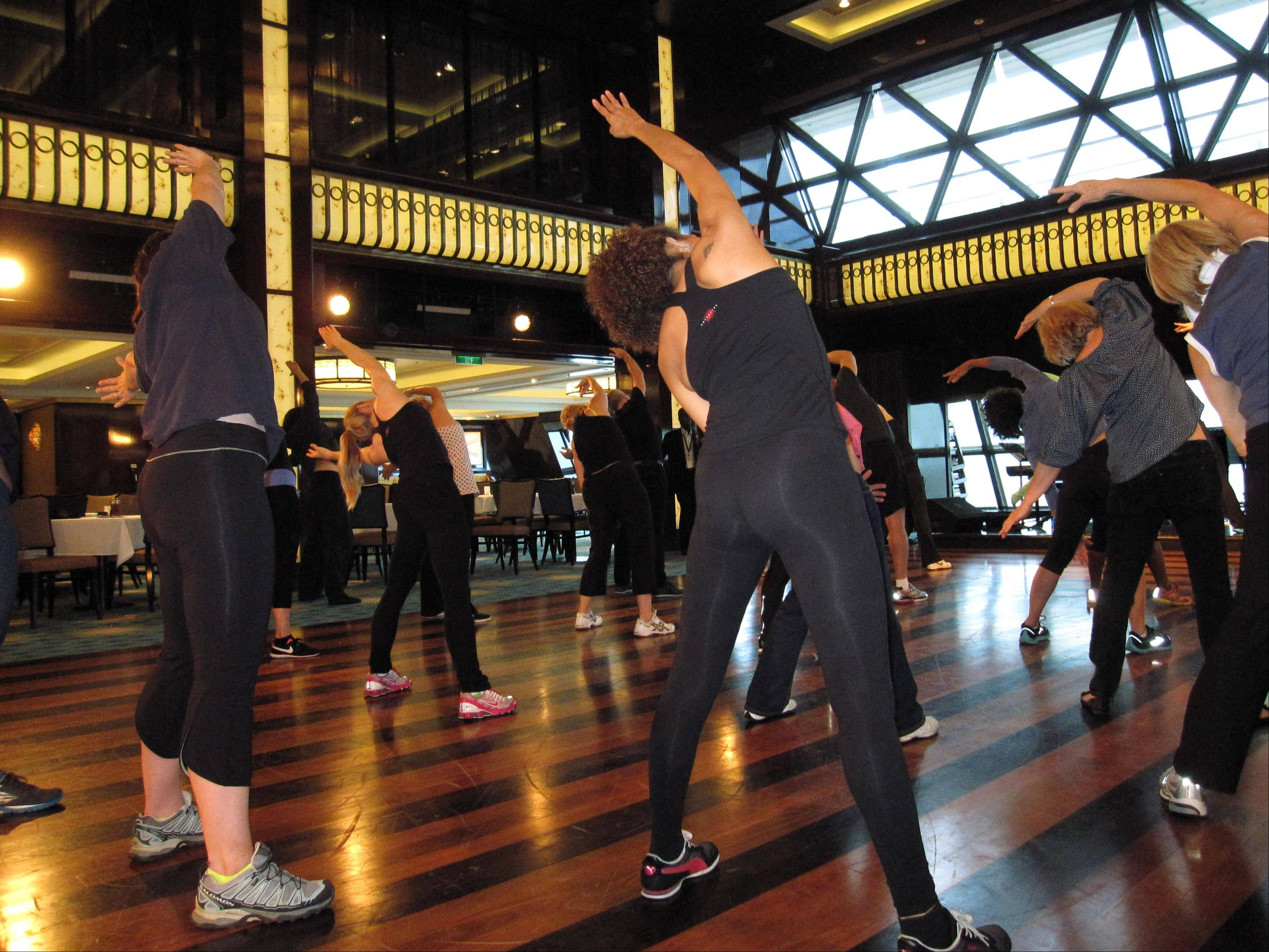 A fitness class designed by the athletic trainer for the Rockettes, Elaine Winslow, is taught to passengers aboard the Norwegian Breakaway cruise ship.