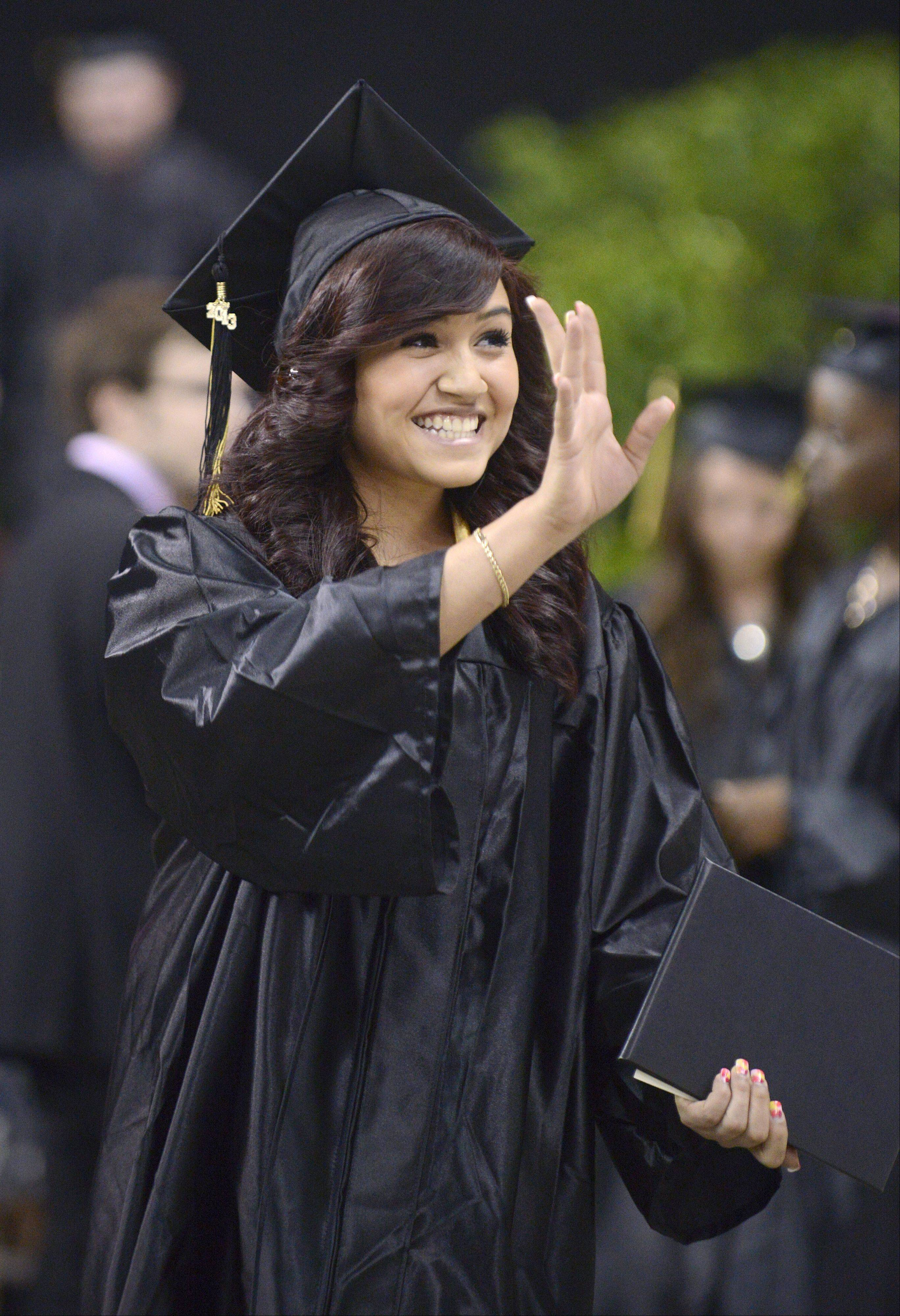 Michelle Jimenez waves to family after receiving her diploma at Streamwood High School's commencement ceremony at the Sears Centre in Hoffman Estates on Saturday, May 25.