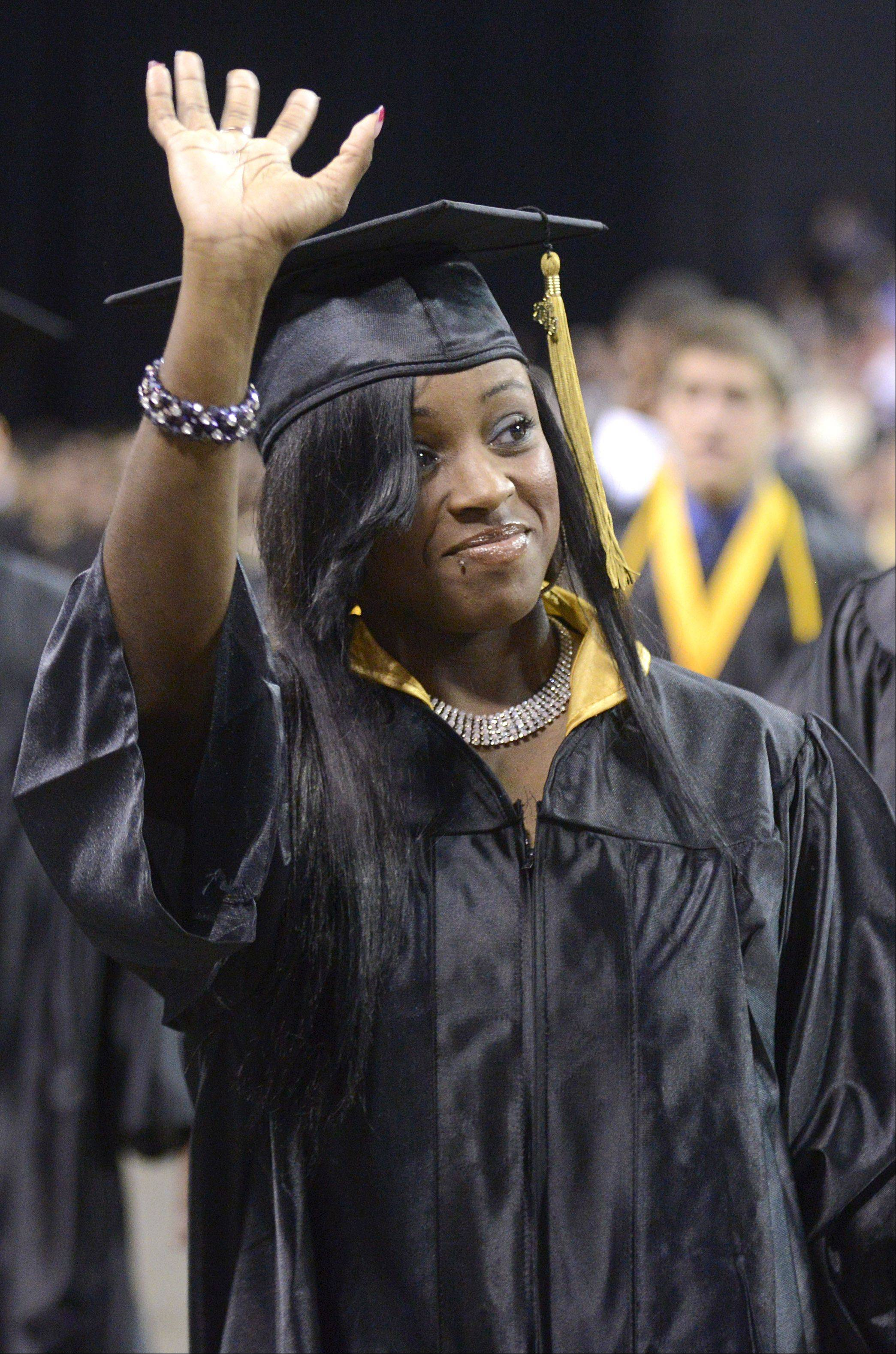 Donielle Ward waves to family as she exits the floor at Streamwood High School's commencement ceremony at the Sears Centre in Hoffman Estates on Saturday, May 25.