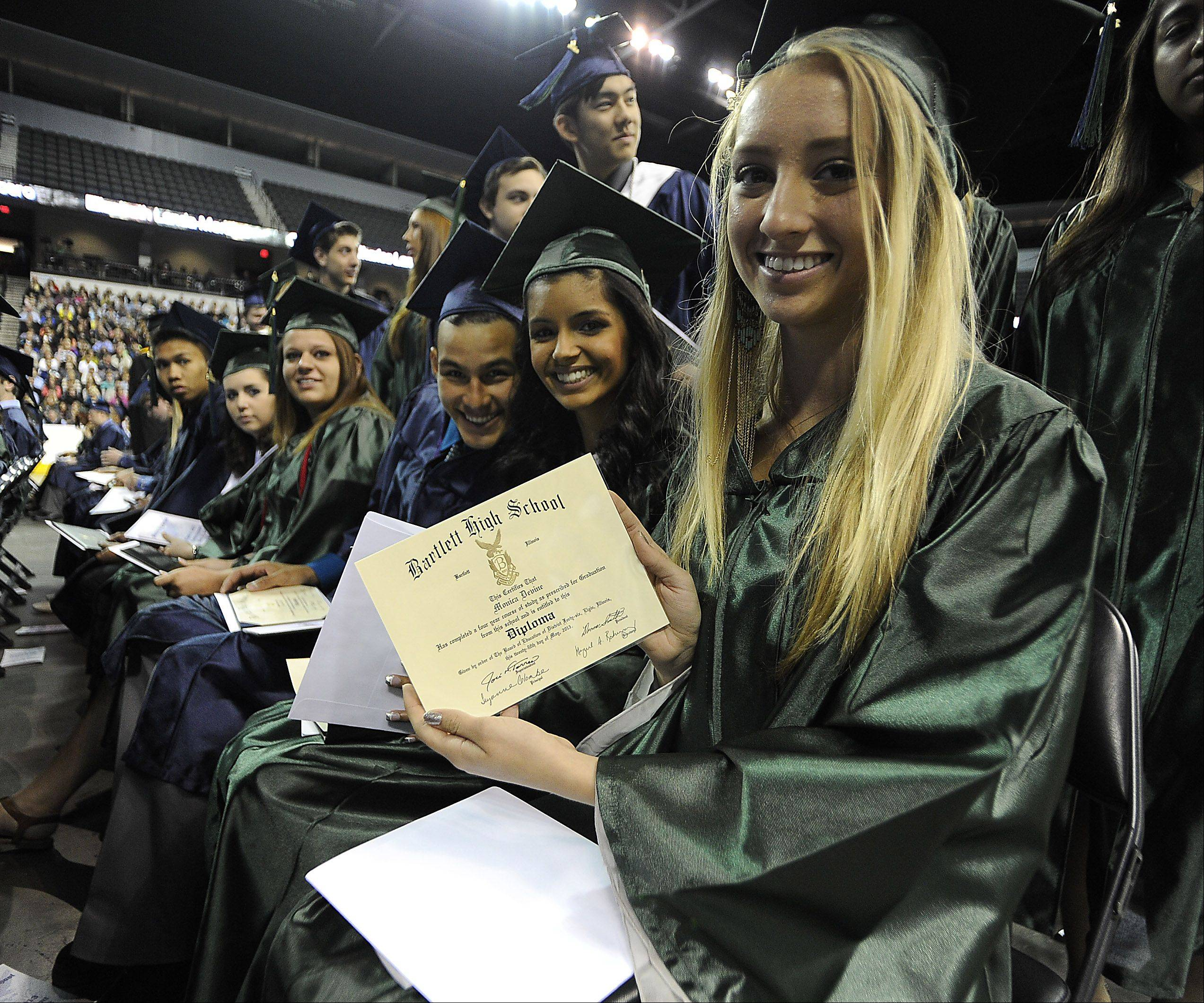 Graduate Monica Devine,17,of Hanover Park shows off her diploma as she takes part in the Bartlett High School Commencement at the Sears Centre in Hoffman Estates on Saturday.