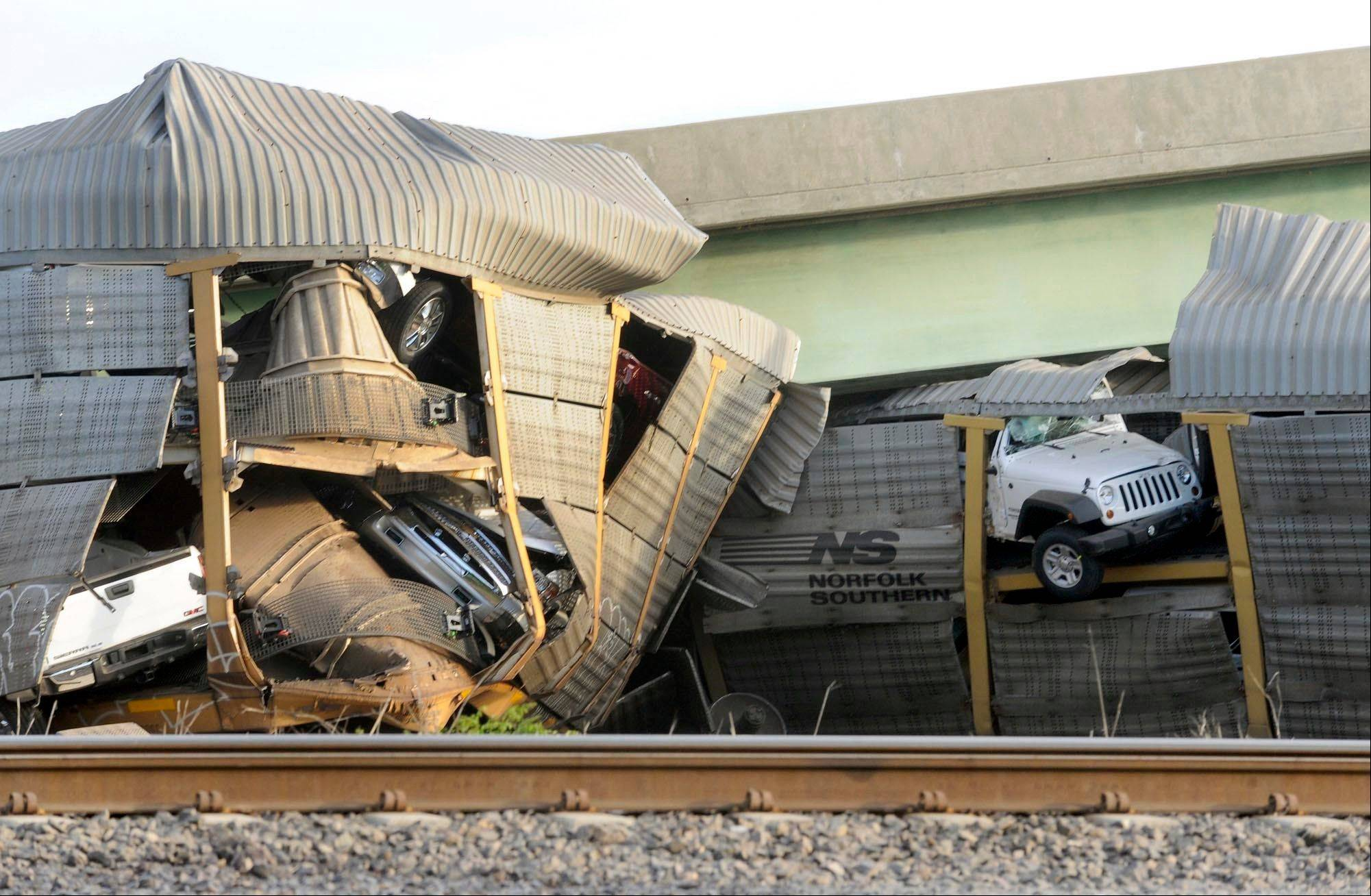 New vehicles being transported on a Burlington Northern Santa Fe train poke out of their damaged rail car.