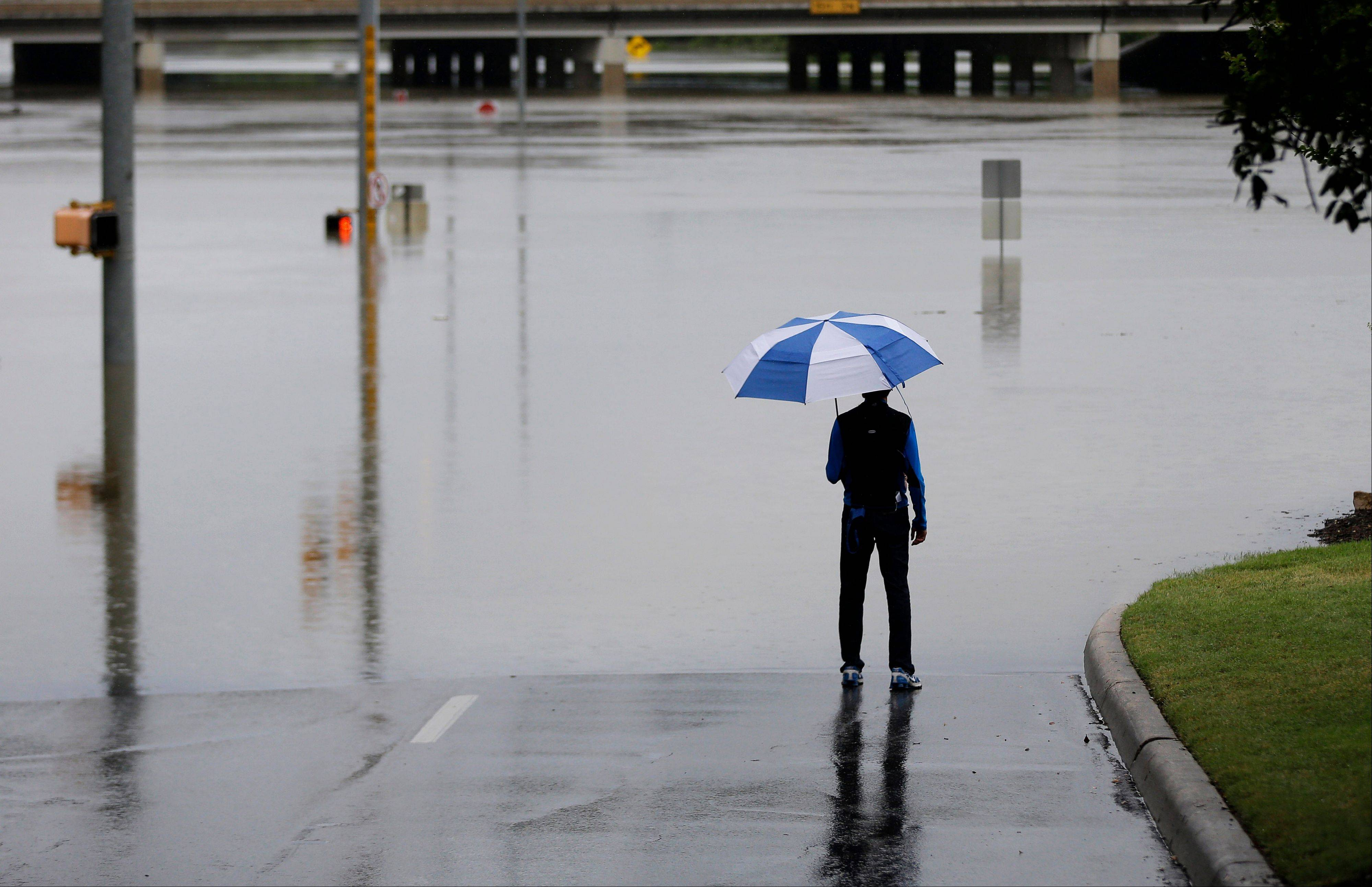 A man surveys floodwaters Saturday caused by heavy rains in San Antonio. The city has received torrential rains since Friday evening.