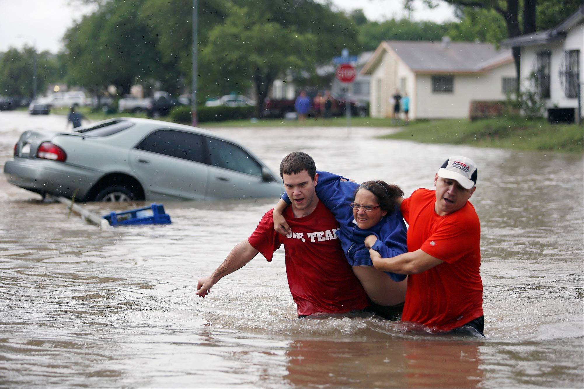 Marco Fairchild, left, and Gary Garza, right, help Sueann Schaller from her car Saturday.