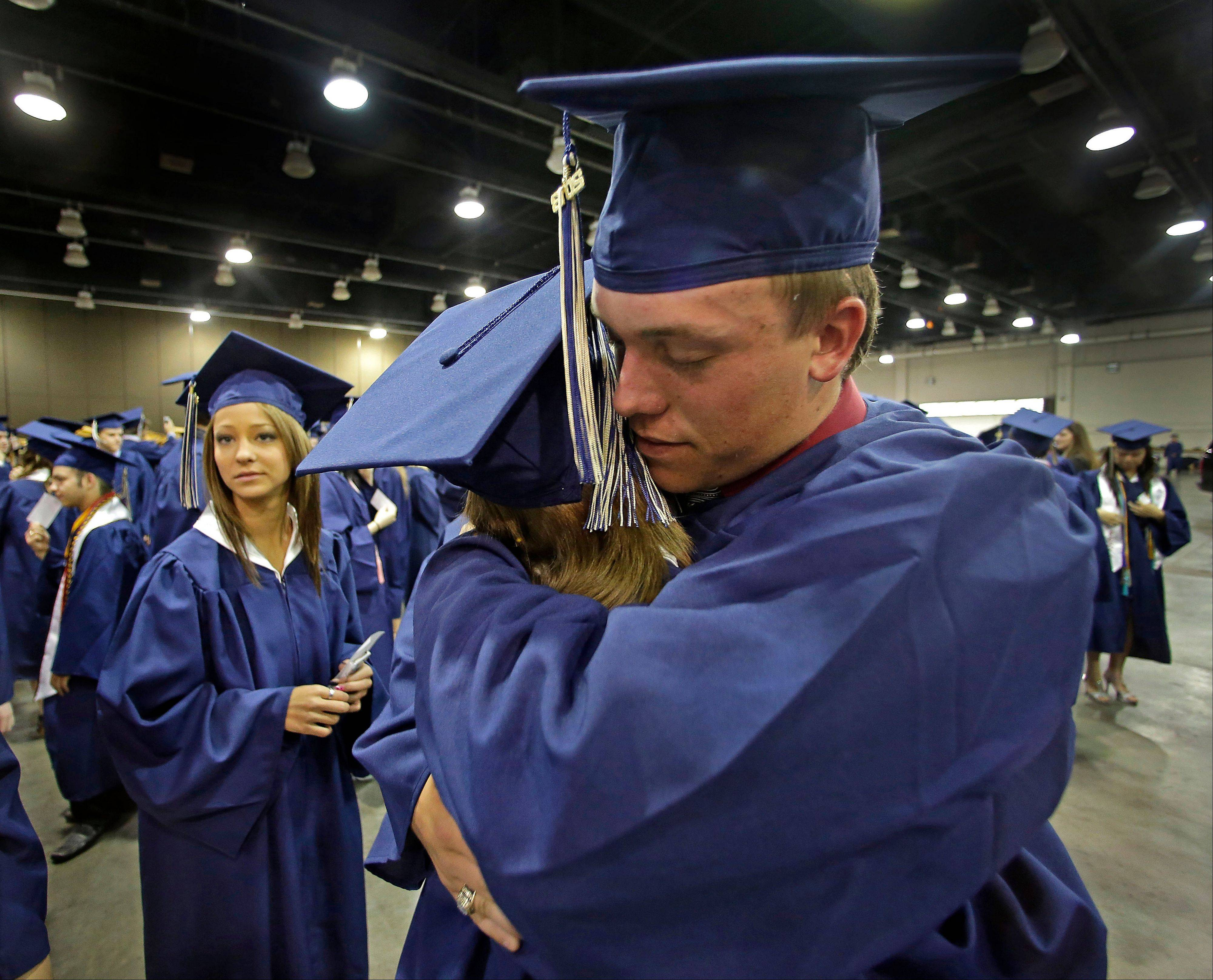Southmoore High School senior Jake Spradling hugs a classmate as they get ready to attend their commencement ceremony.