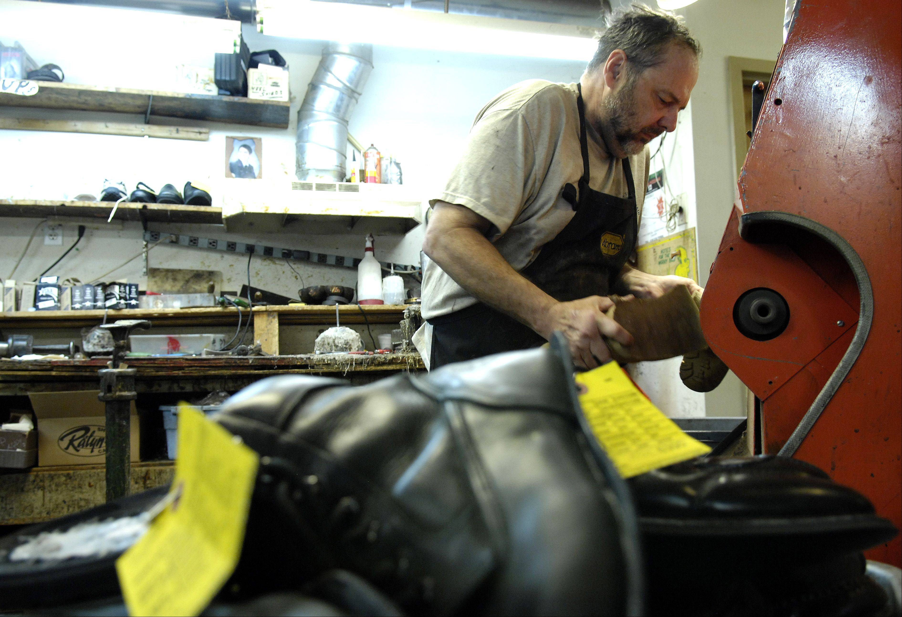 Gary Miller of Geneva Shoe Repair works at the grinder last week. The third-generation family business is celebrating its 30th anniversary this month.