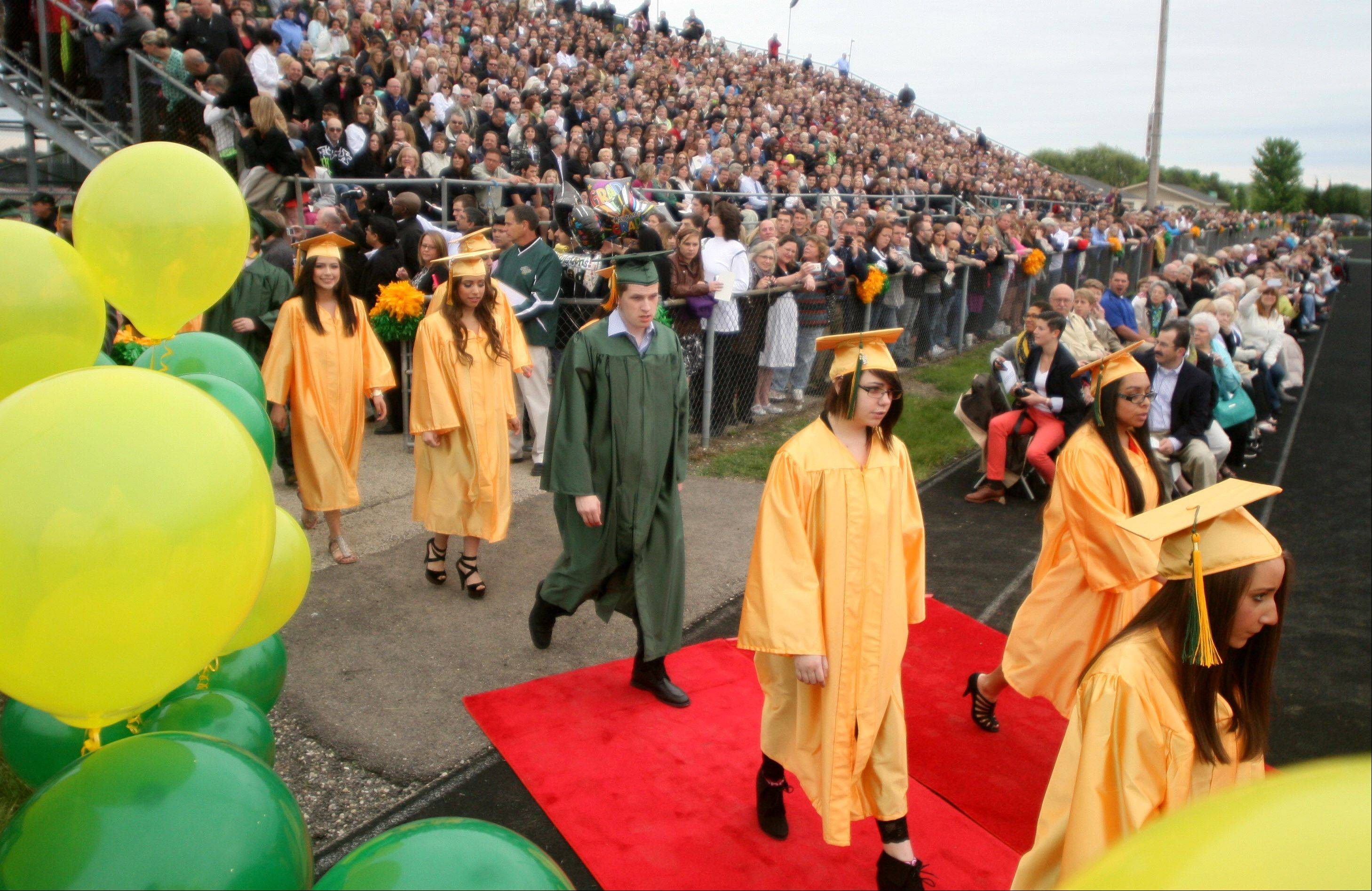 Members of the class of 2013 file in as part of commencement exercises at Crystal Lake South High School on Saturday at Ken Bruhn Field on the campus of Crystal Lake South.
