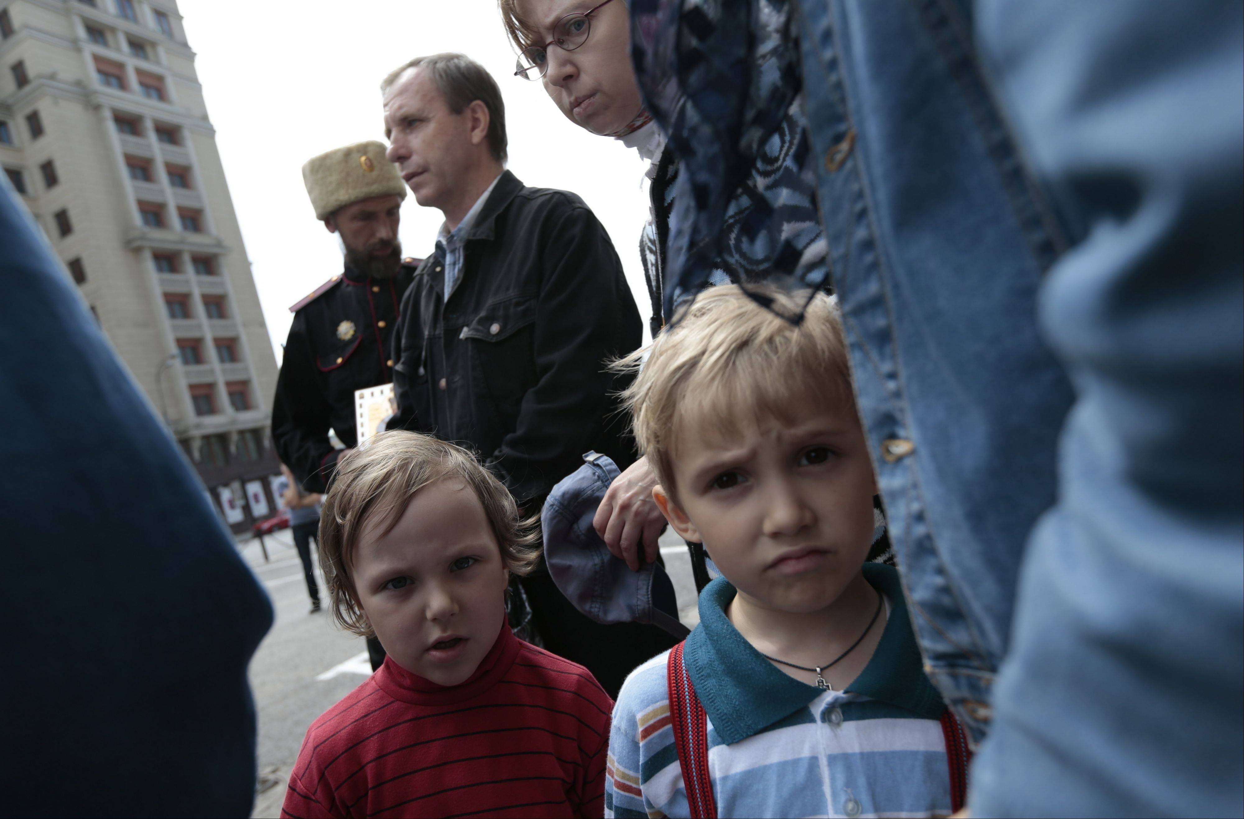 "Associated PressOrthodox Christians stand protesting against a gay rally in Moscow, Saturday, May 25. The Kremlin initiated a bill banning ""propaganda of homosexuality"" and routinely banned gay rallies and parade. Russian police say they detained at least 30 gay rights campaigners and their opponents at an unsanctioned rally in Moscow."