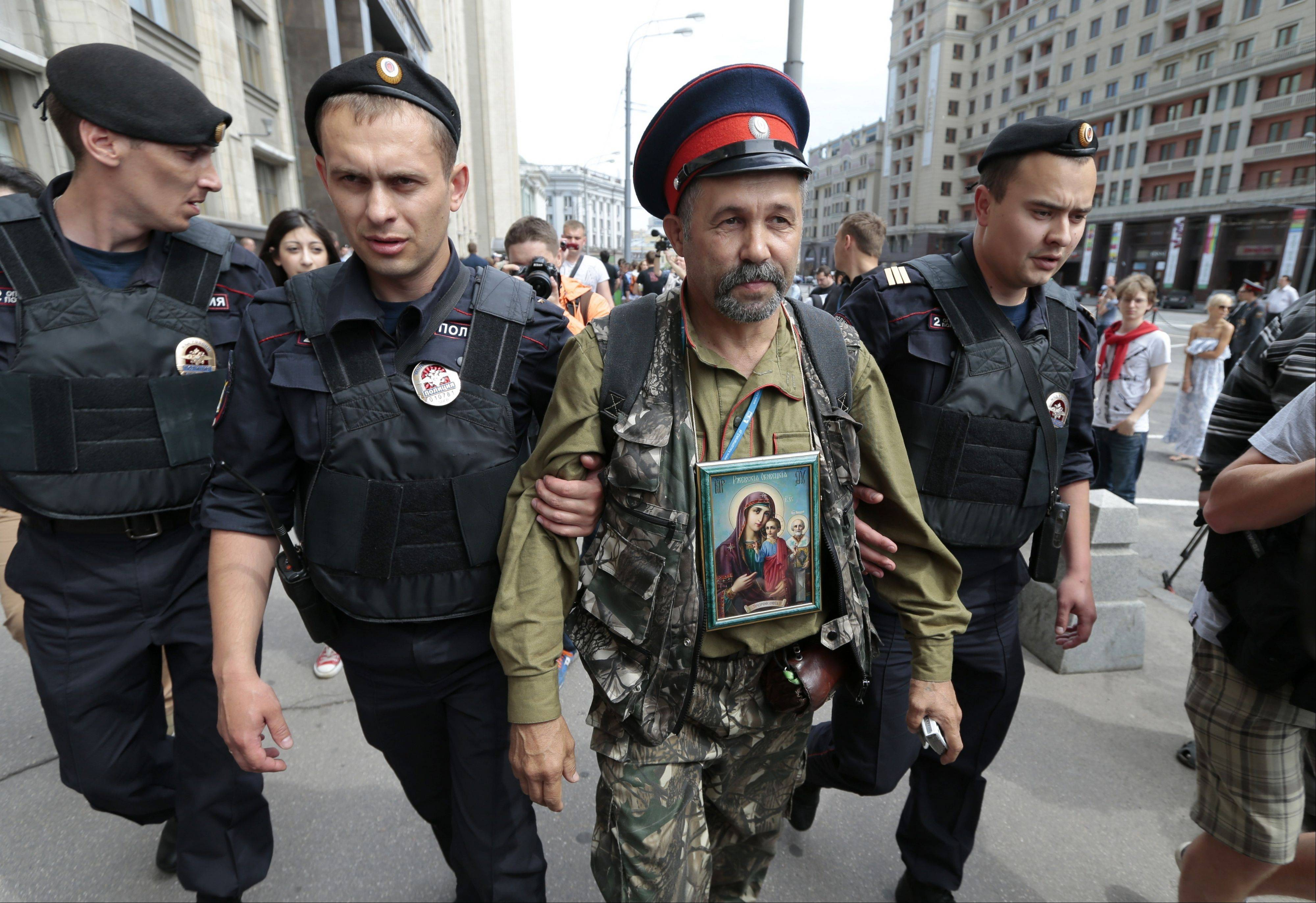 "Associated PressPolice detain an anti-gay protester wearing a Cossack hat and an Orthodox Christian icon during an unsanctioned gay rally in downtown Moscow, Saturday, May 25. The Kremlin initiated a bill banning ""propaganda of homosexuality"" and routinely banned gay rallies and parade."